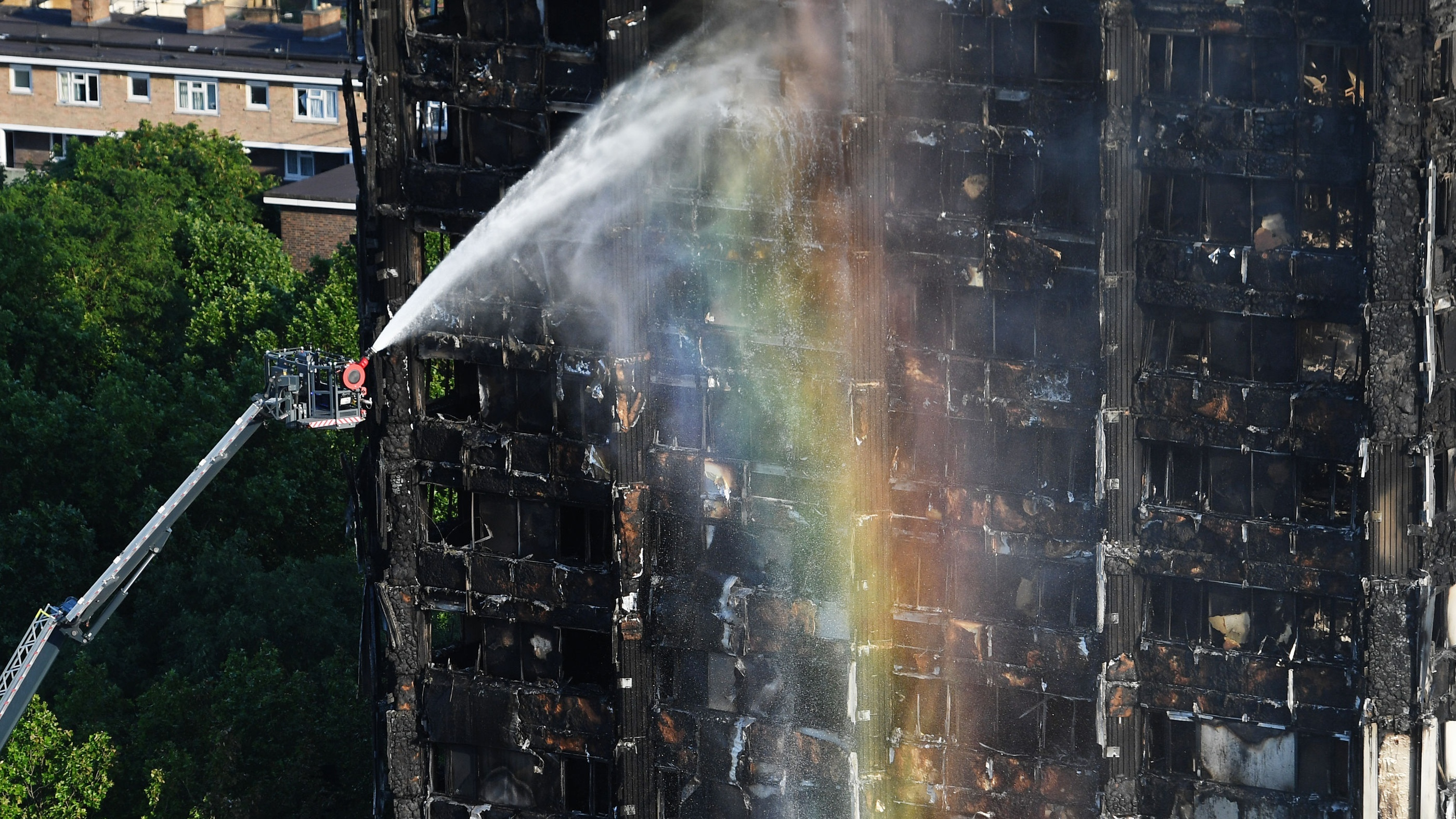Firefighters spray water after a fire engulfed the 24-storey Grenfell Tower (Victoria Jones/PA)