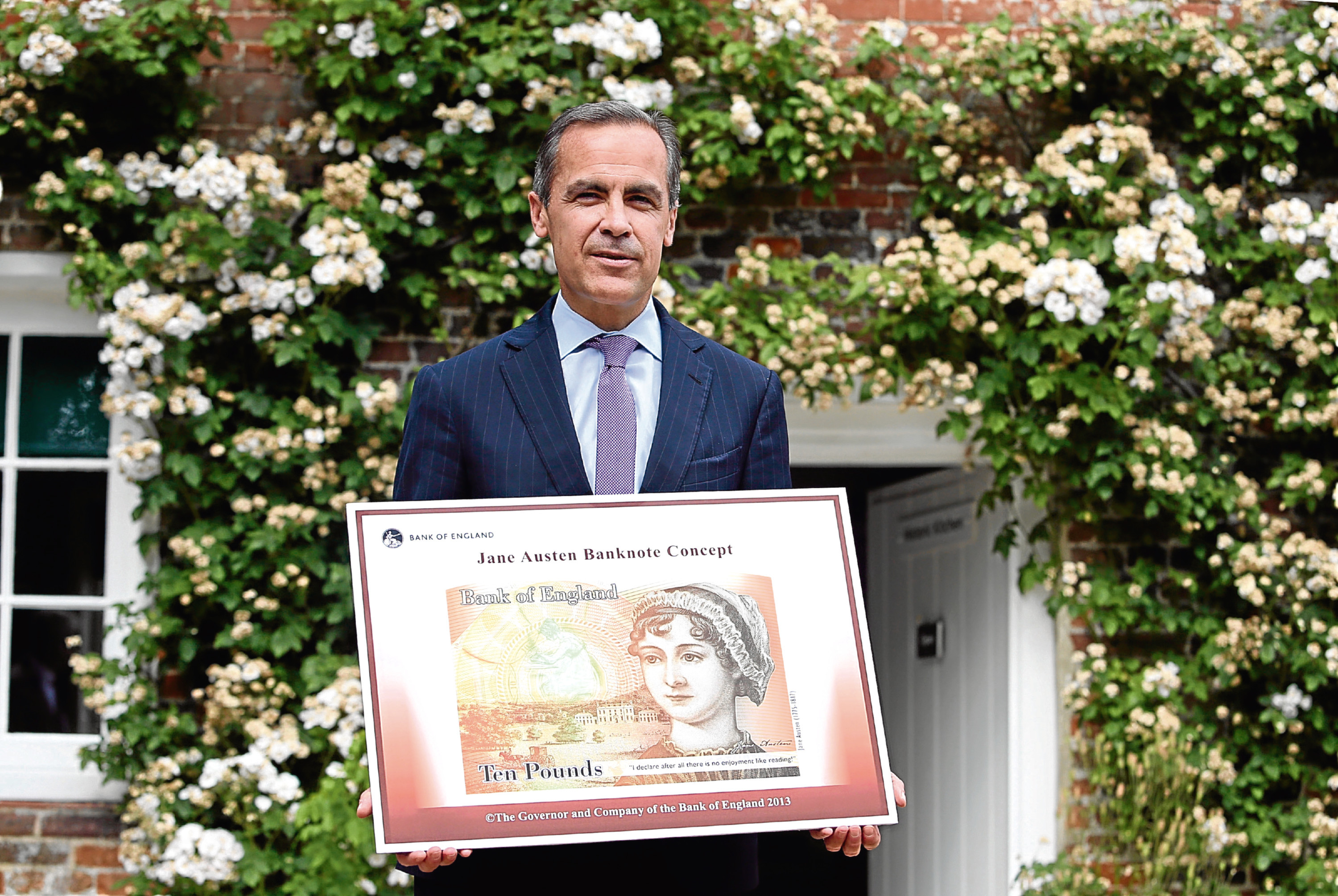 Governor of the Bank of England, Mark Carney stands holding the concept design for the new Bank of England ten pound banknote, featuring author Jane Austen, following the presentation at the Jane Austen House Museum , (Pool/Getty Images)