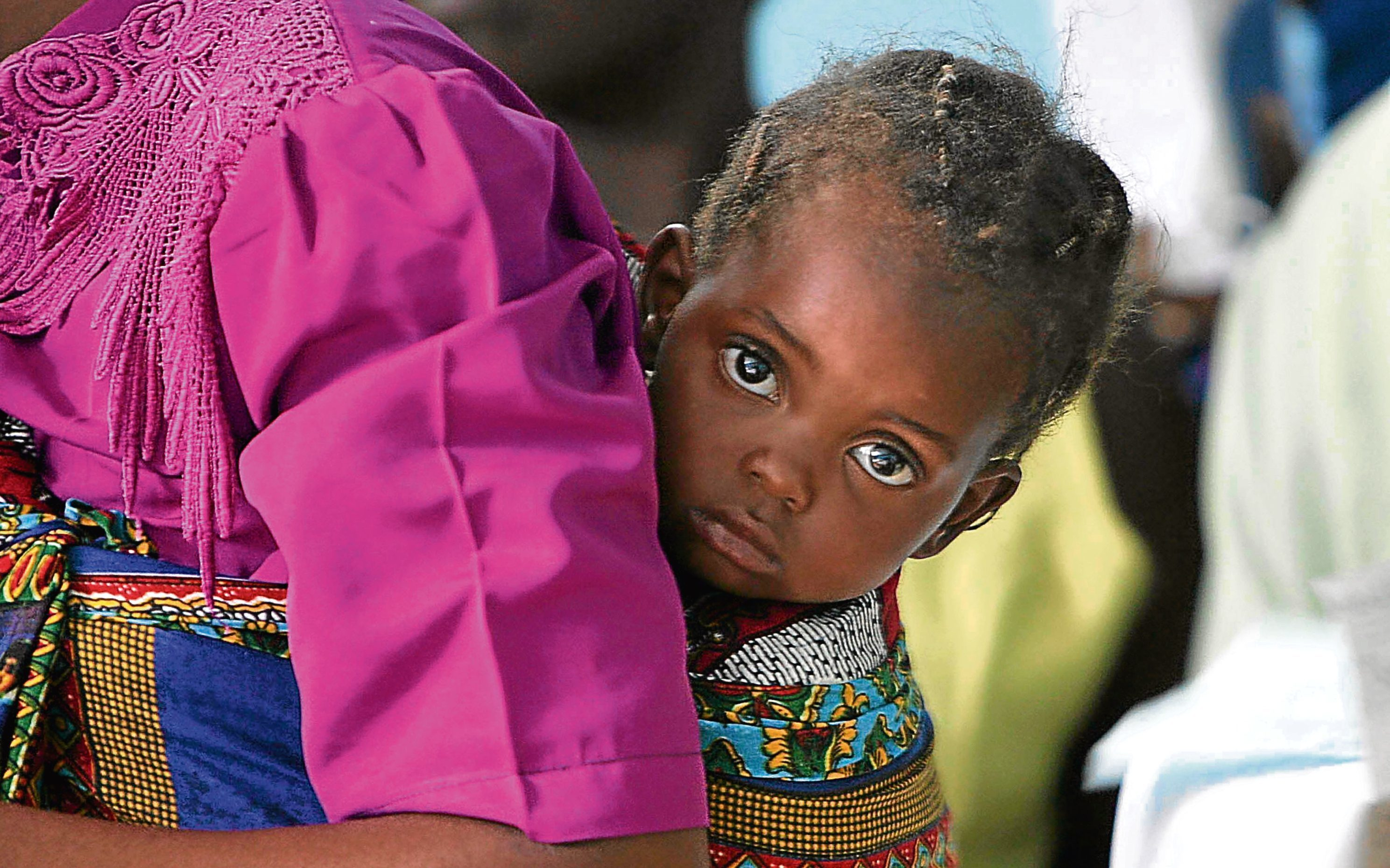 A young girl is seen on the back of her mother whilst she waits for treatment at Kamuzu Hospital, Malawi (Chris Jackson/Getty Images)