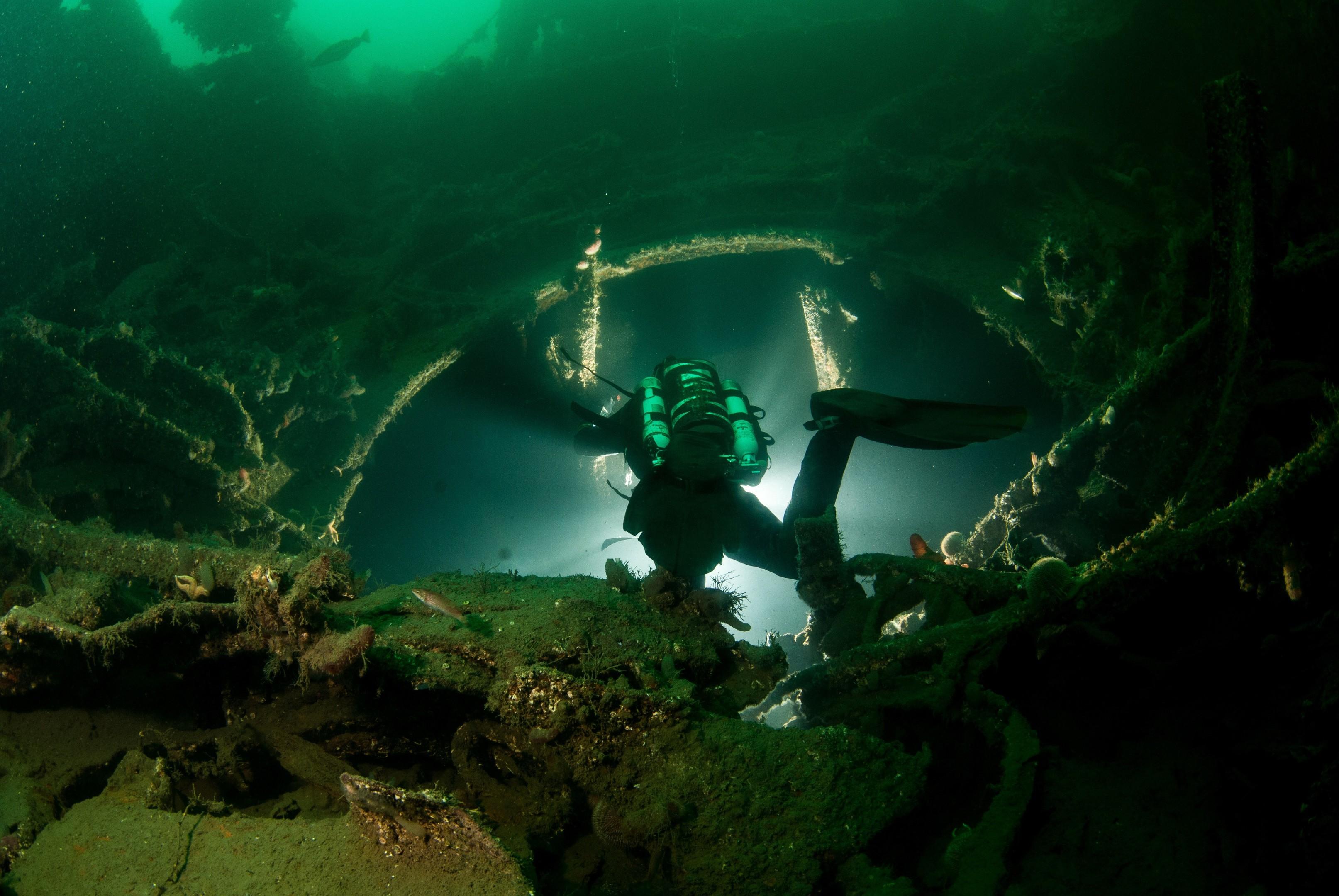 A diver descends into the base of Cäeser turret barbette (Bob Anderson)