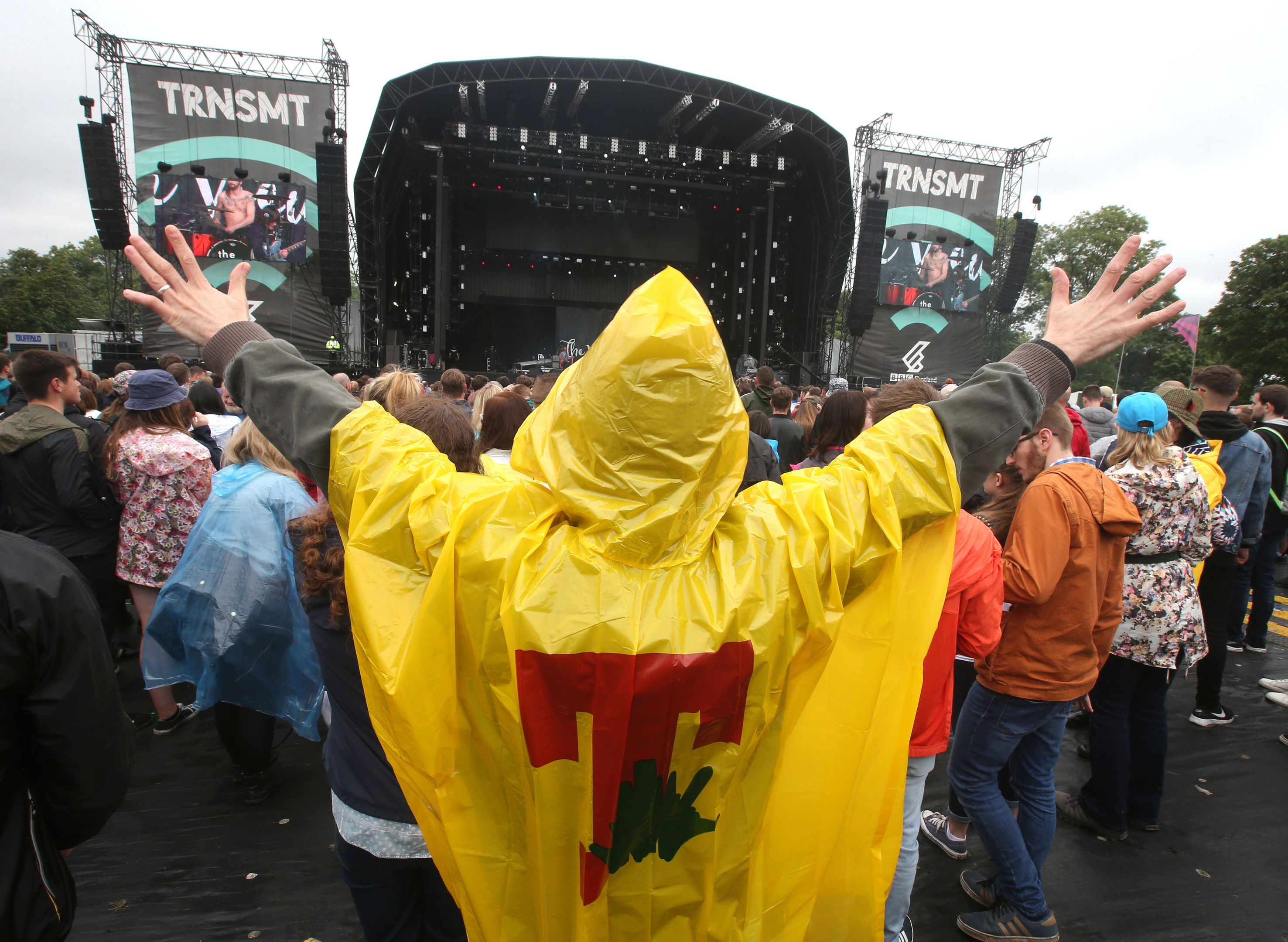 A music fan wears a T in the Park branded poncho as he listens to music on the main stage at the TRNSMT festival in Glasgow. (Andrew Milligan/PA Wire)