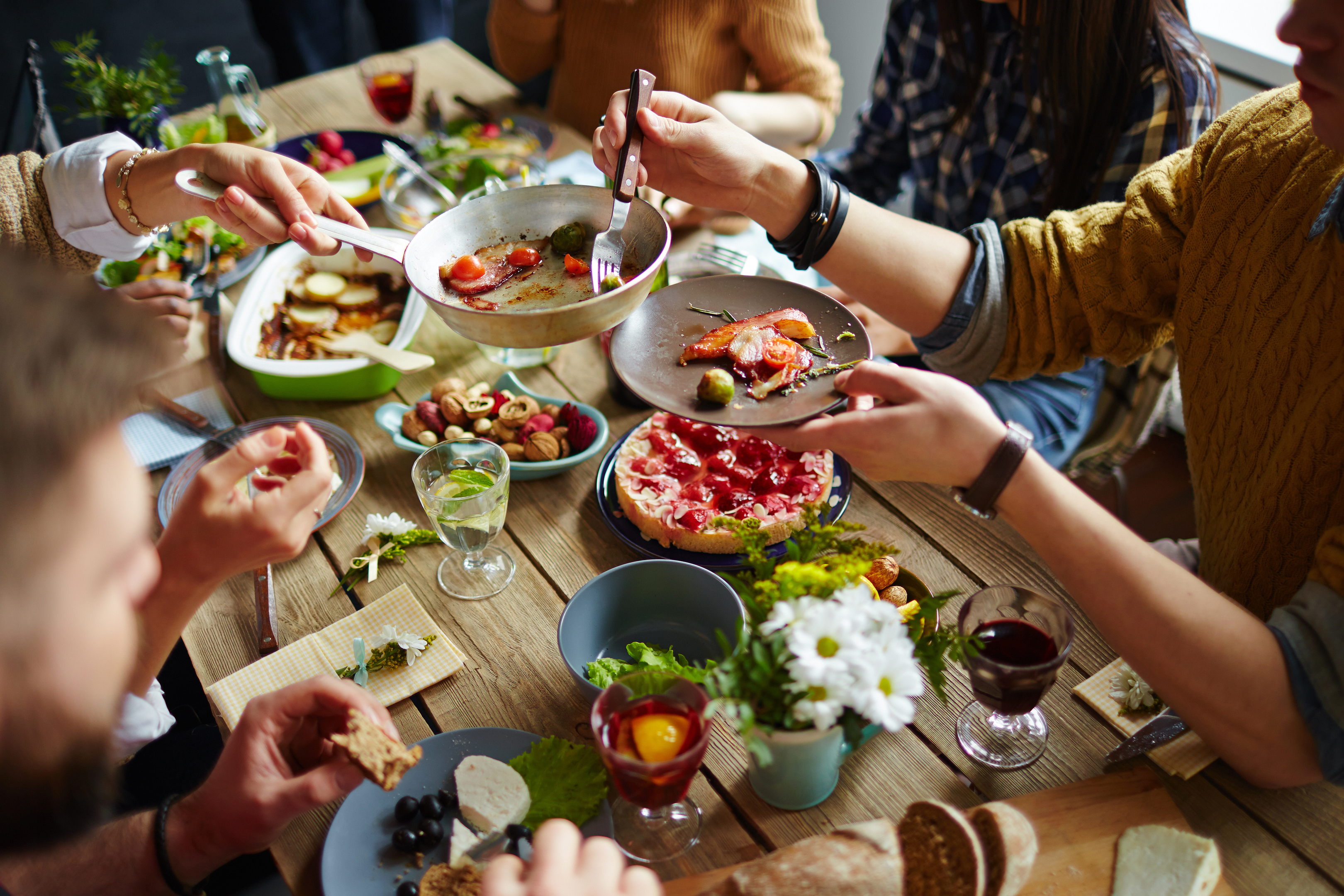 People sitting at dining table and eating (iStock)