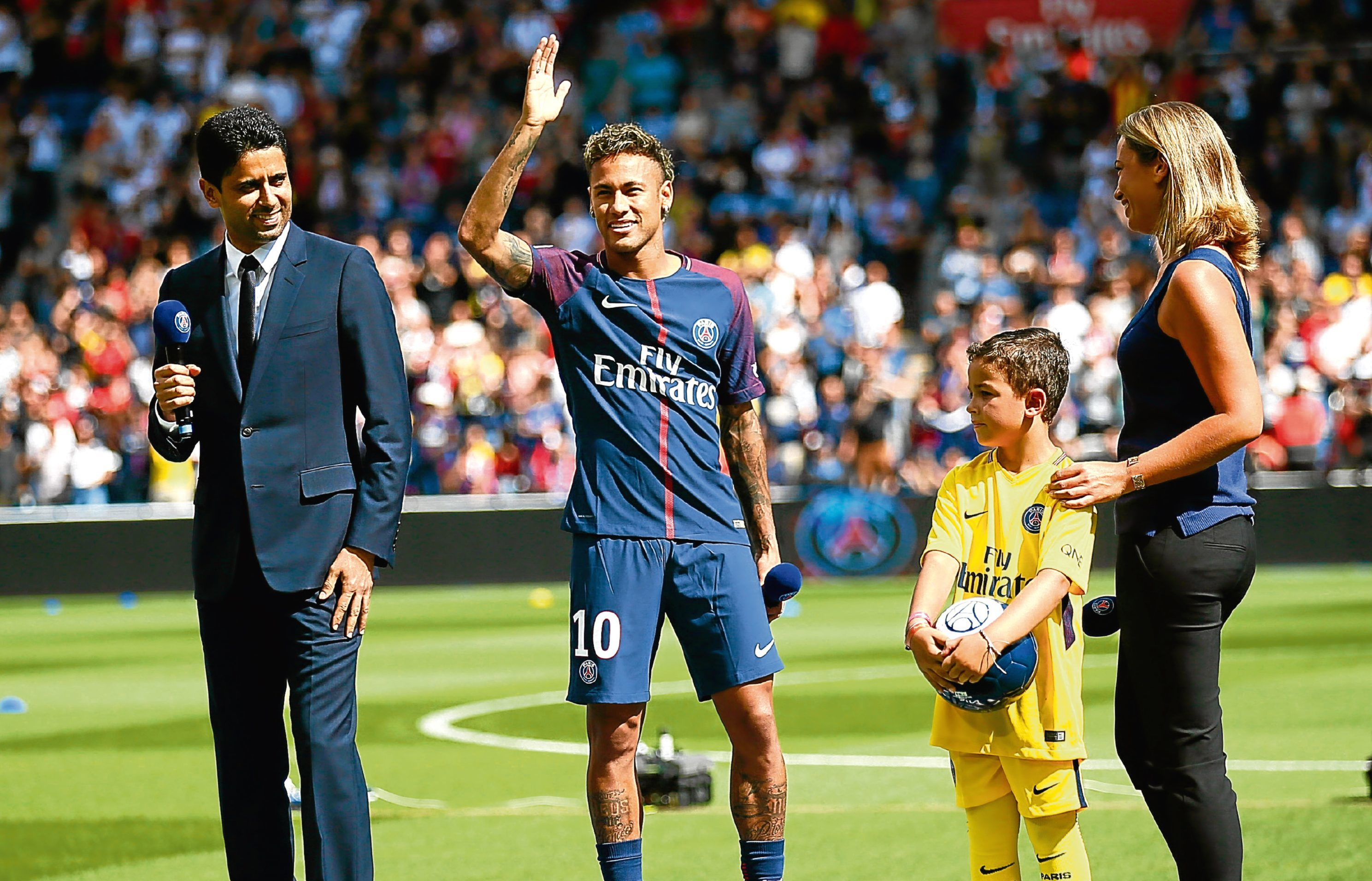 Neymar waves to fans as he stands next to PSG president Nasser Ghanim Al-Khelaïfi at the Parc des Princes (AP Photo/Francois Mori)