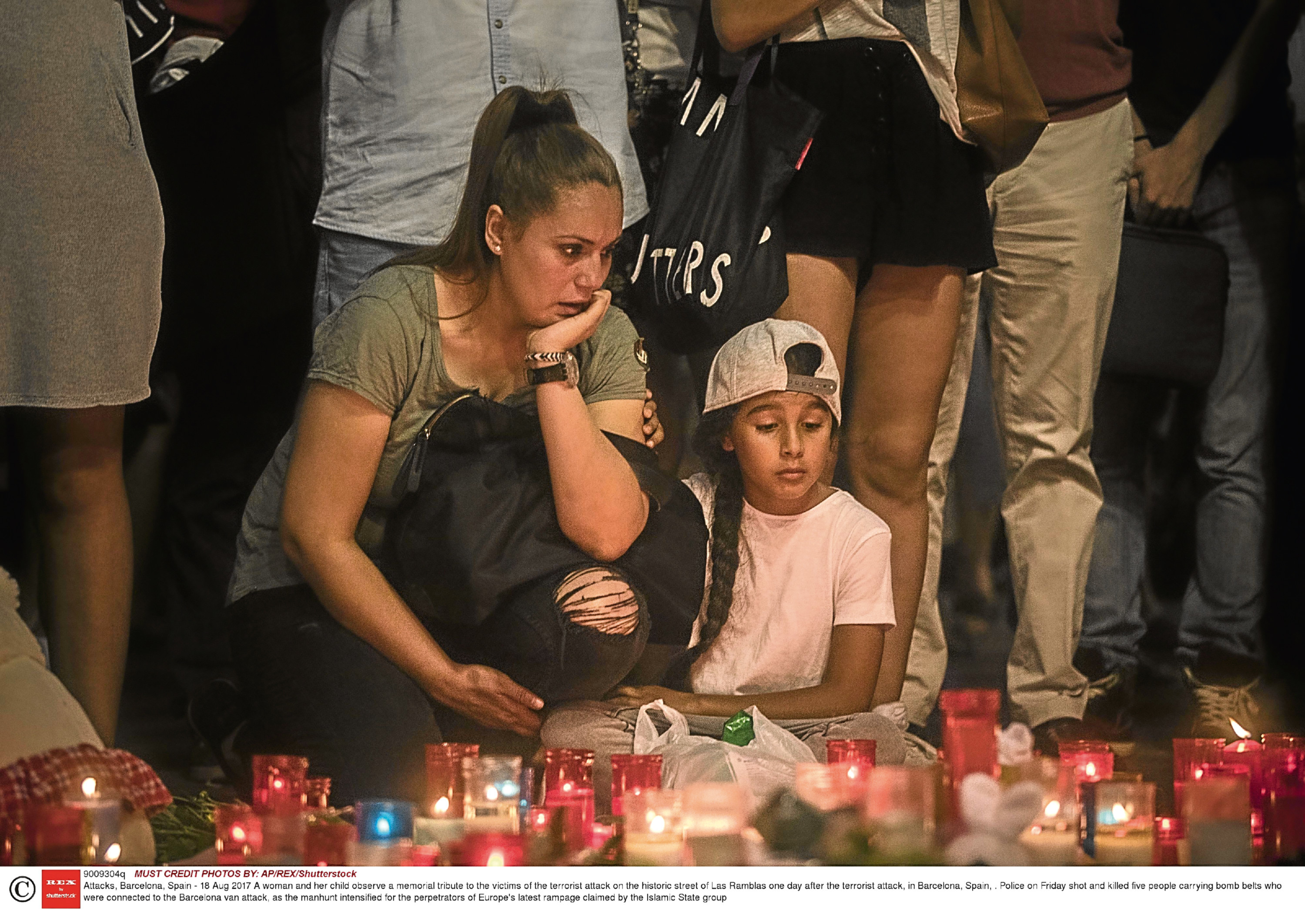 A woman and her child observe a memorial tribute to the victims of the terrorist attack, in Barcelona (AP/REX/Shutterstock)