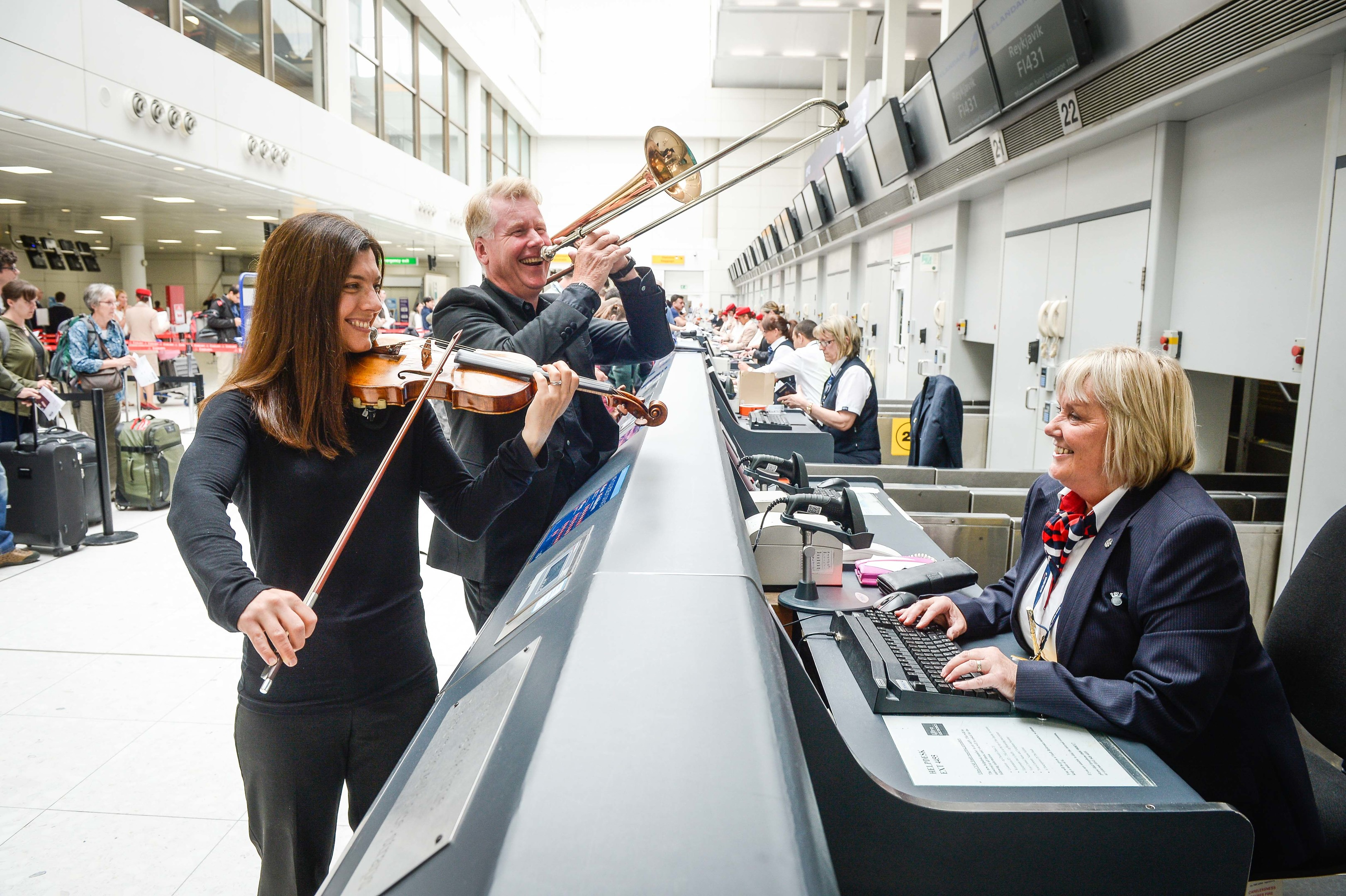 Passengers at Glasgow Airport today were invited to exercise their voices with the backing of the Royal Scottish National Orchestra (RSNO) and accompanied by dancers from Dance House Glasgow, as the nationÕs popular air terminal marks its 50th anniversary. l-r RSNO musicians Susannah Lowdon (Violin) and Lance Green (Trombone) with British Airways check in staff Linda Friel (Nick Ponty)