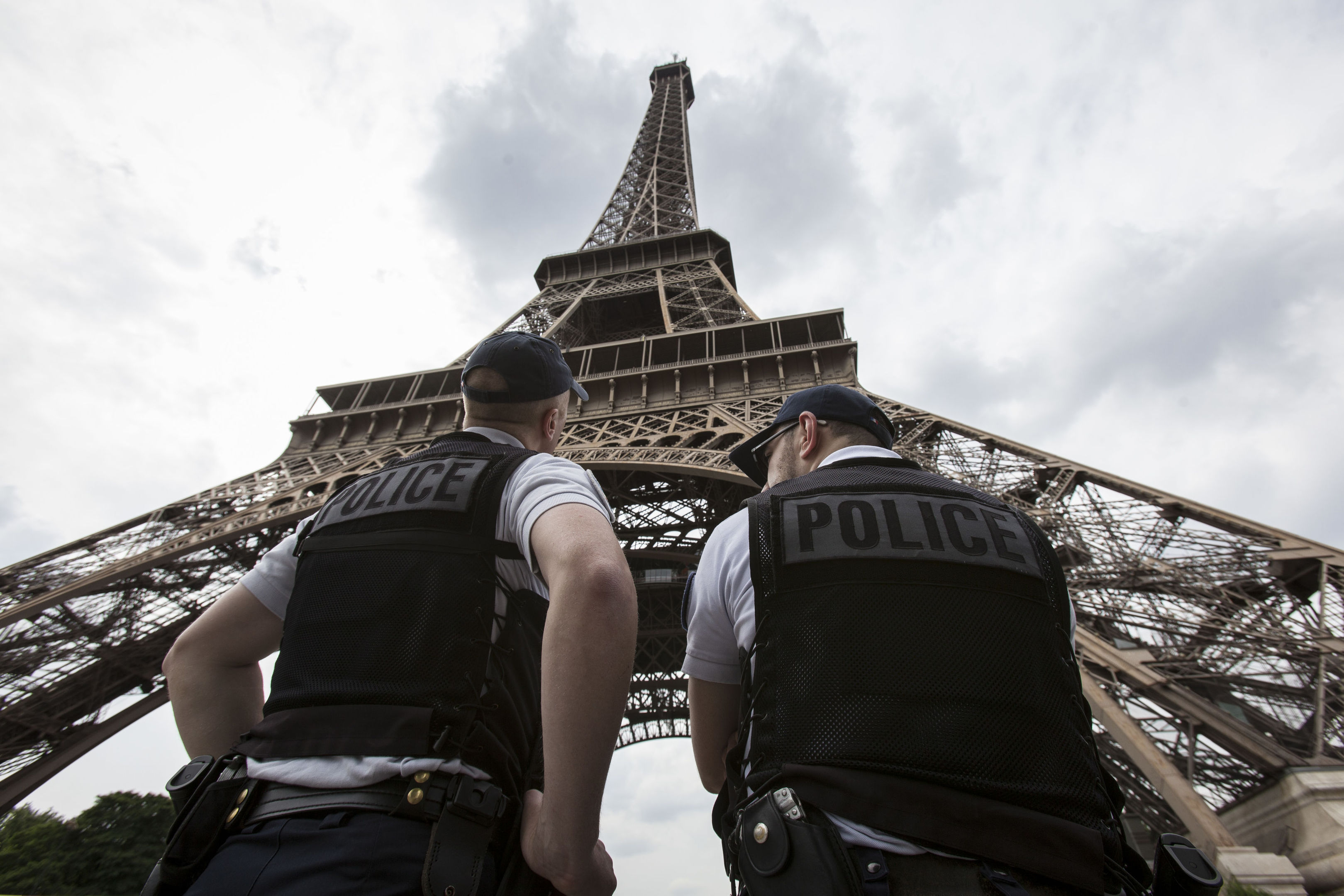 French riot police officers patrol under the Eiffel Tower, in Paris. A young French man who recently was discharged from a psychiatric hospital is under investigation for glorifying terrorism after he brandished a knife and tried to breach security at the Eiffel Tower, authorities said Sunday, Aug. 6, 2017. (AP Photo/Kamil Zihnioglu, File)