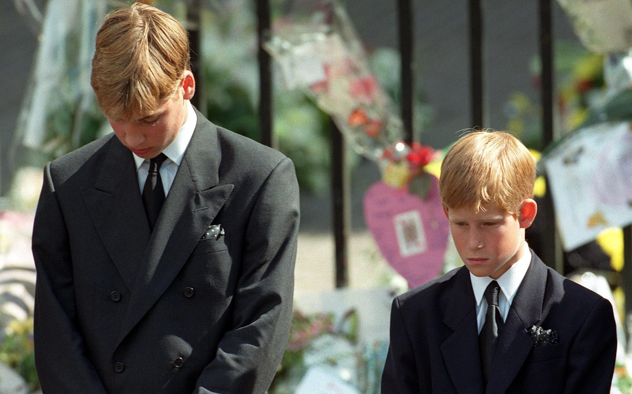 Prince William (left) and Prince Harry, the sons of Diana, Princess of Wales, bow their heads as their mother's coffin is taken out of Westminster Abbey following her funeral service (Adam Butler/PA Wire)