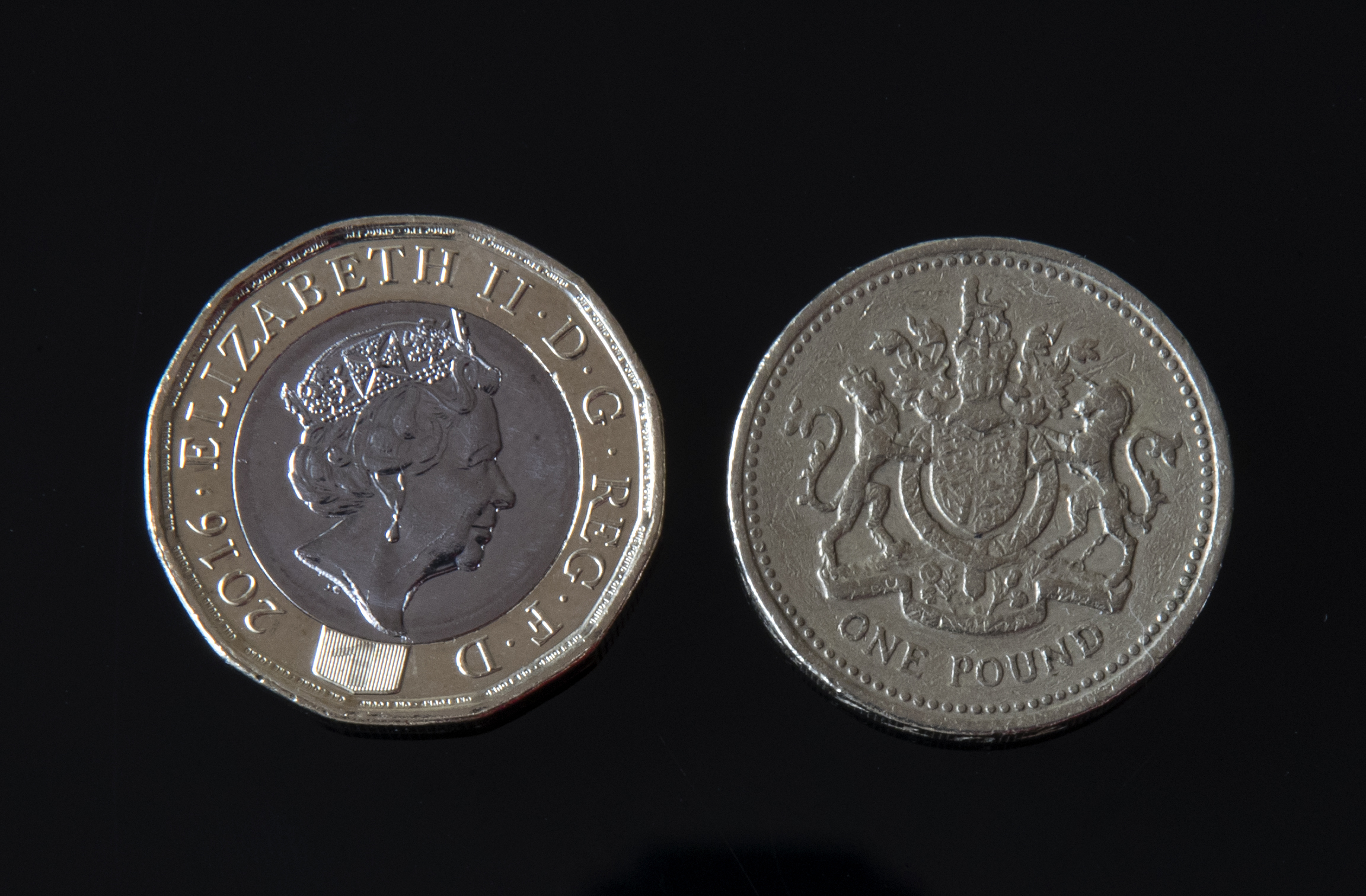 A new 12-sided £1 coin (left) alongside an old £1 coin (Peter Byrne/PA Wire)