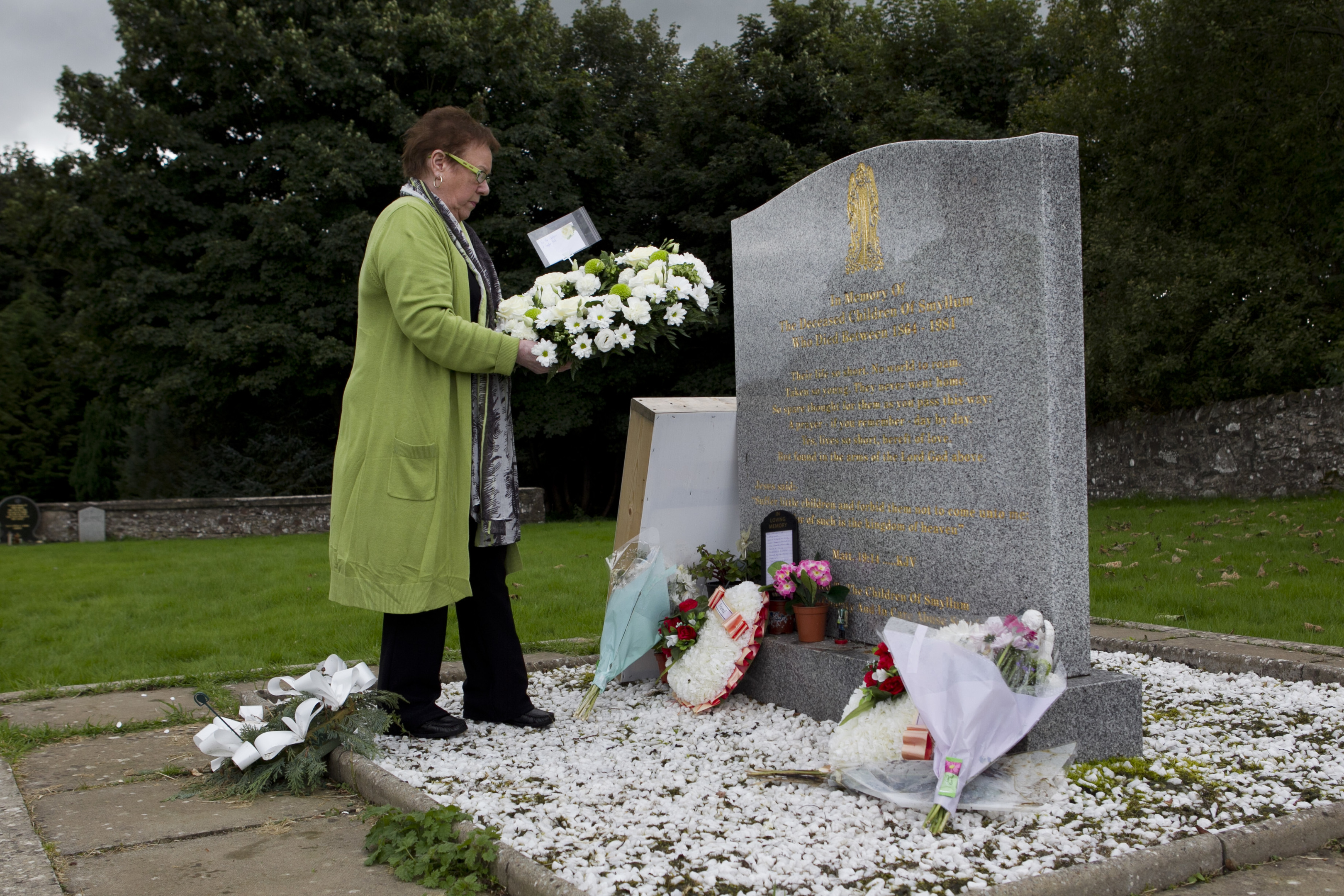 Former Smyllum resident Josie Drage-Dawes laying a wreath at the headstone for the children who died at Smyllum Park Orphange (Andrew Cawley / DC Thomson)