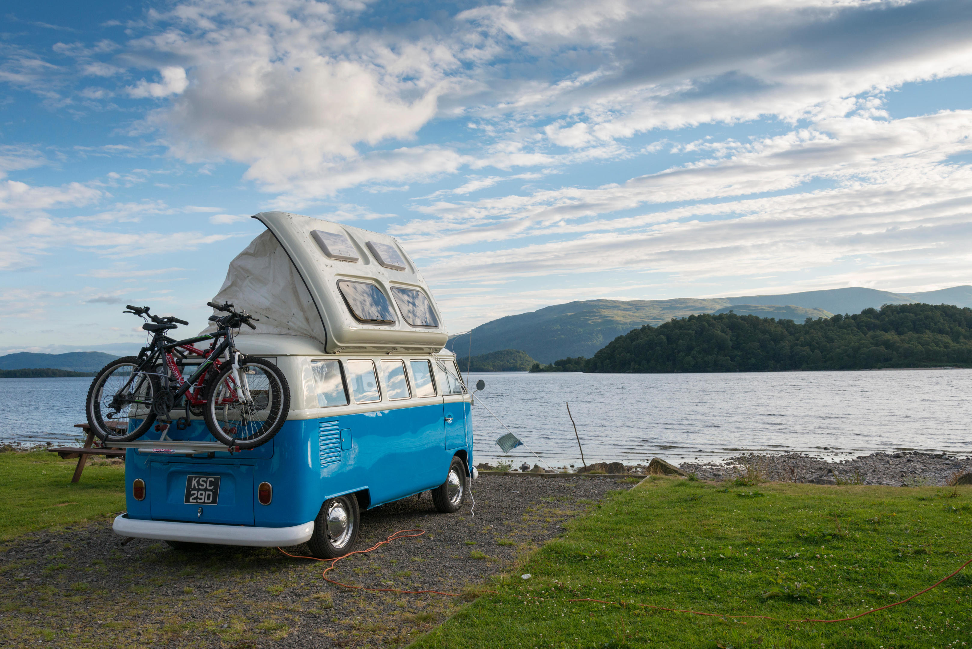 A blue VW campervan parked on the shore of Loch Lomond Scotland UK in summer (Alamy)