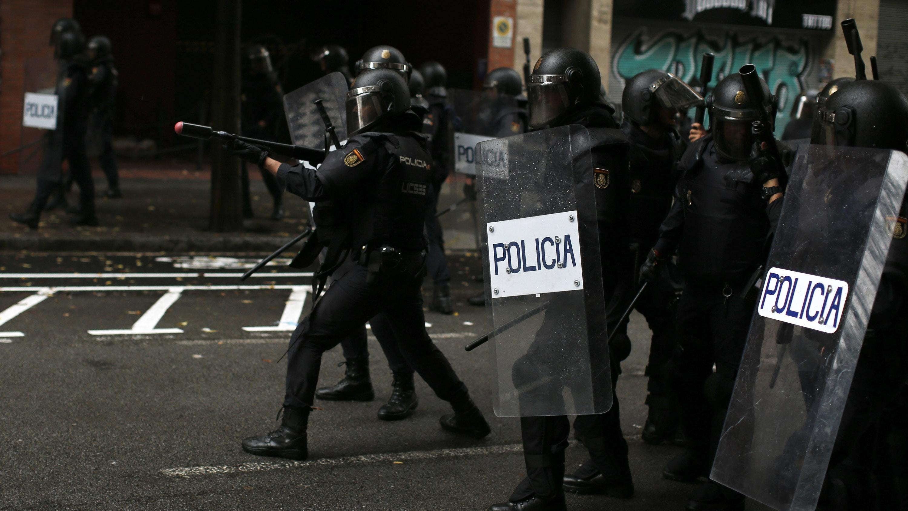A Spanish National Police officer aims rubber-bullet rifle at pro-referendum supporters (Manu Fernandez/AP)