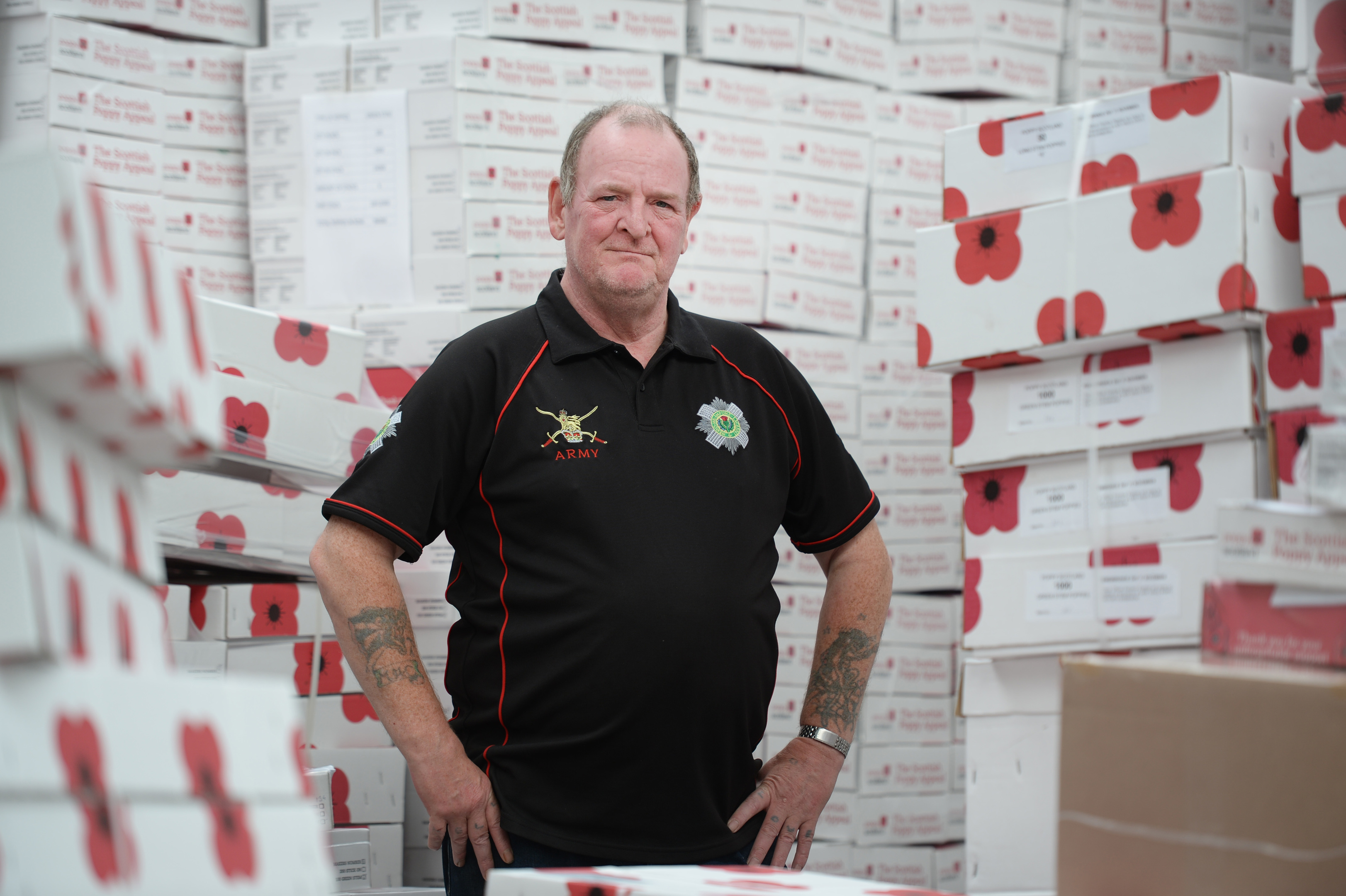Veteran Donald with boxes of poppies