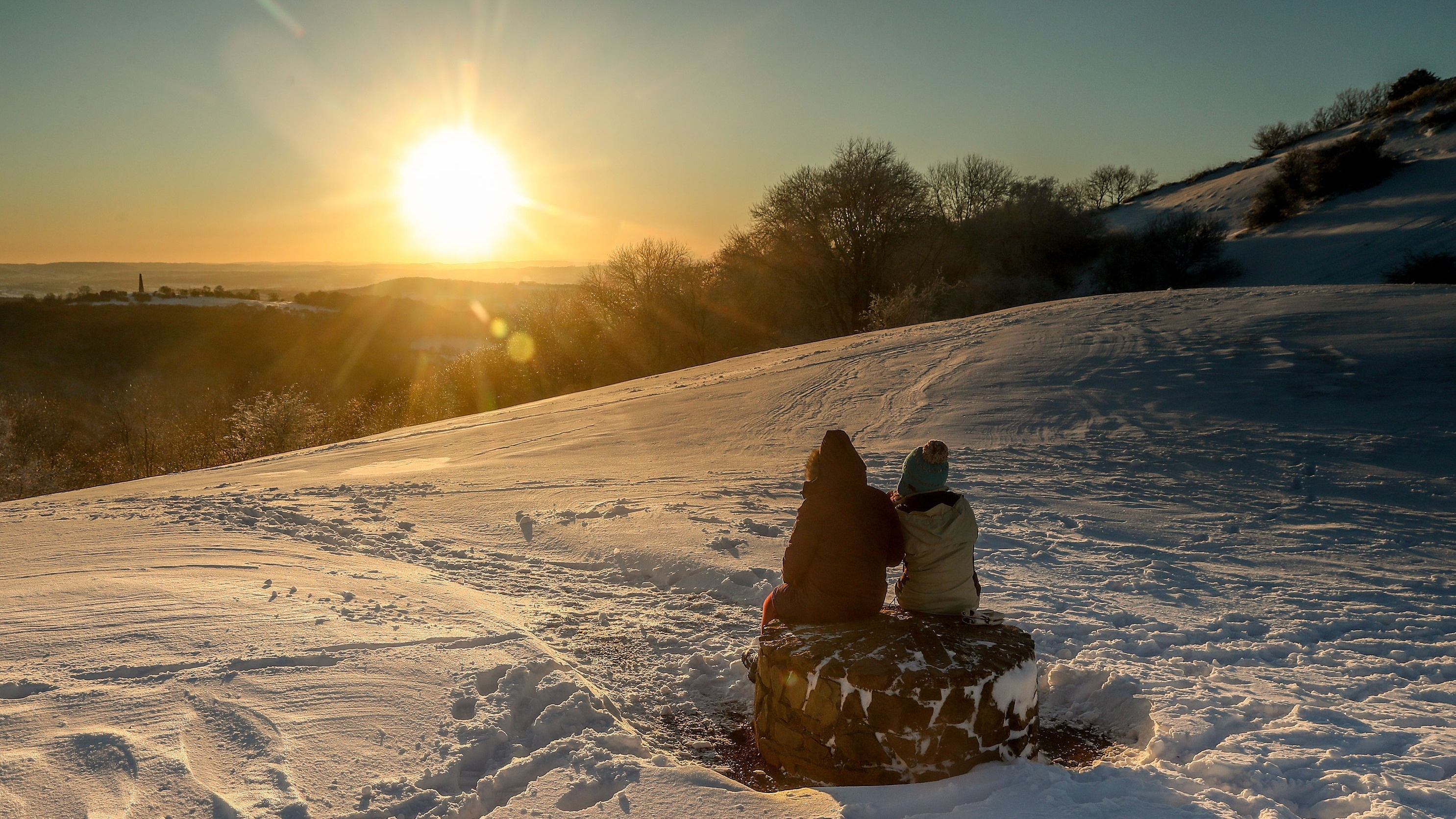 A couple take a rest on the Malvern Hills as the sun sets over Herefordshire (David Davies/PA)