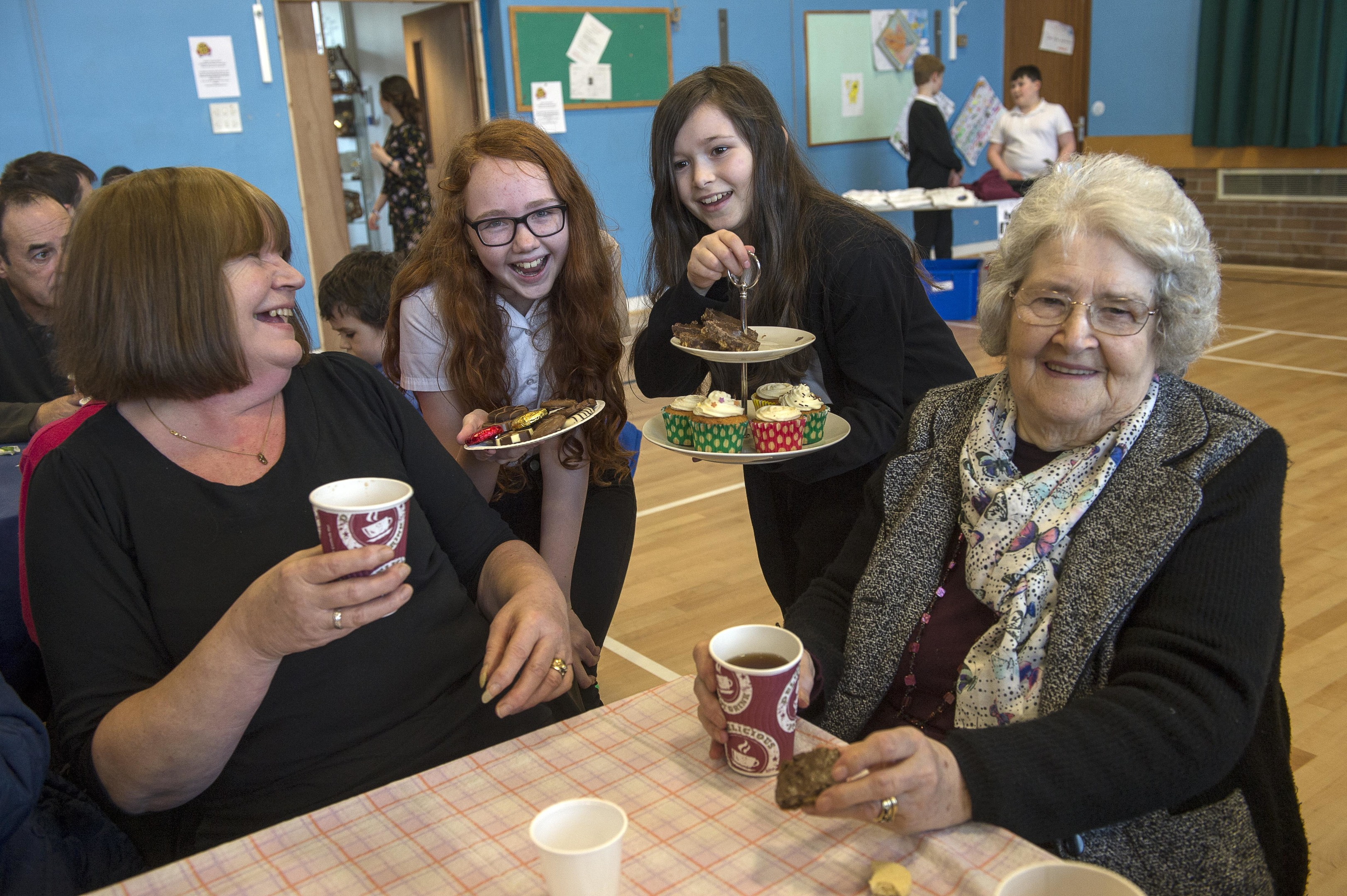 Pupils Rebecca Campbell and Charlotte Mackenzie share a laugh and a some home bakes with Christine Macrae and Agnes Macleod (Trevor Martin)