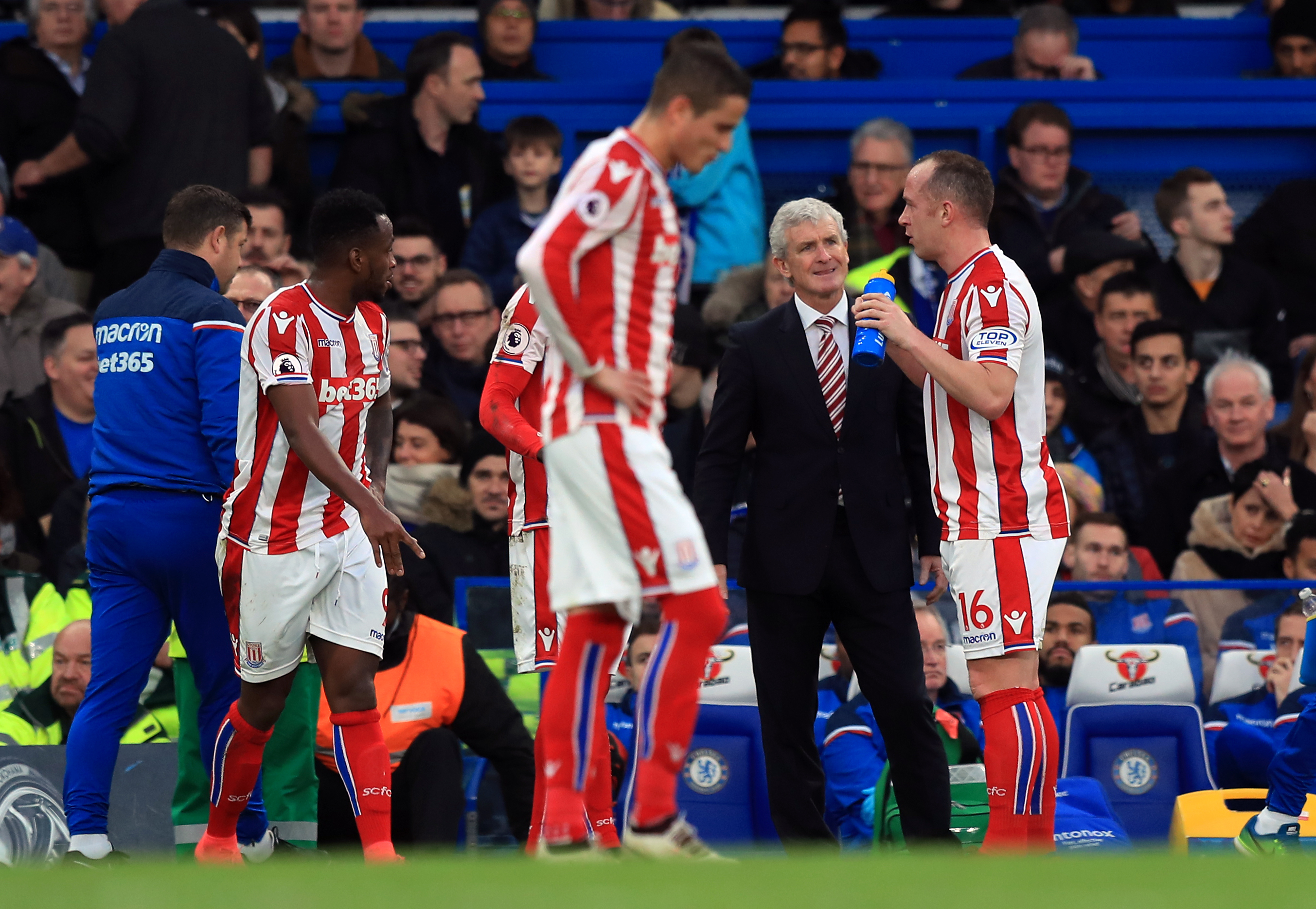 Stoke City manager Mark Hughes speaks to Charlie Adam during the Premier League match at Stamford Bridge, London (PA)