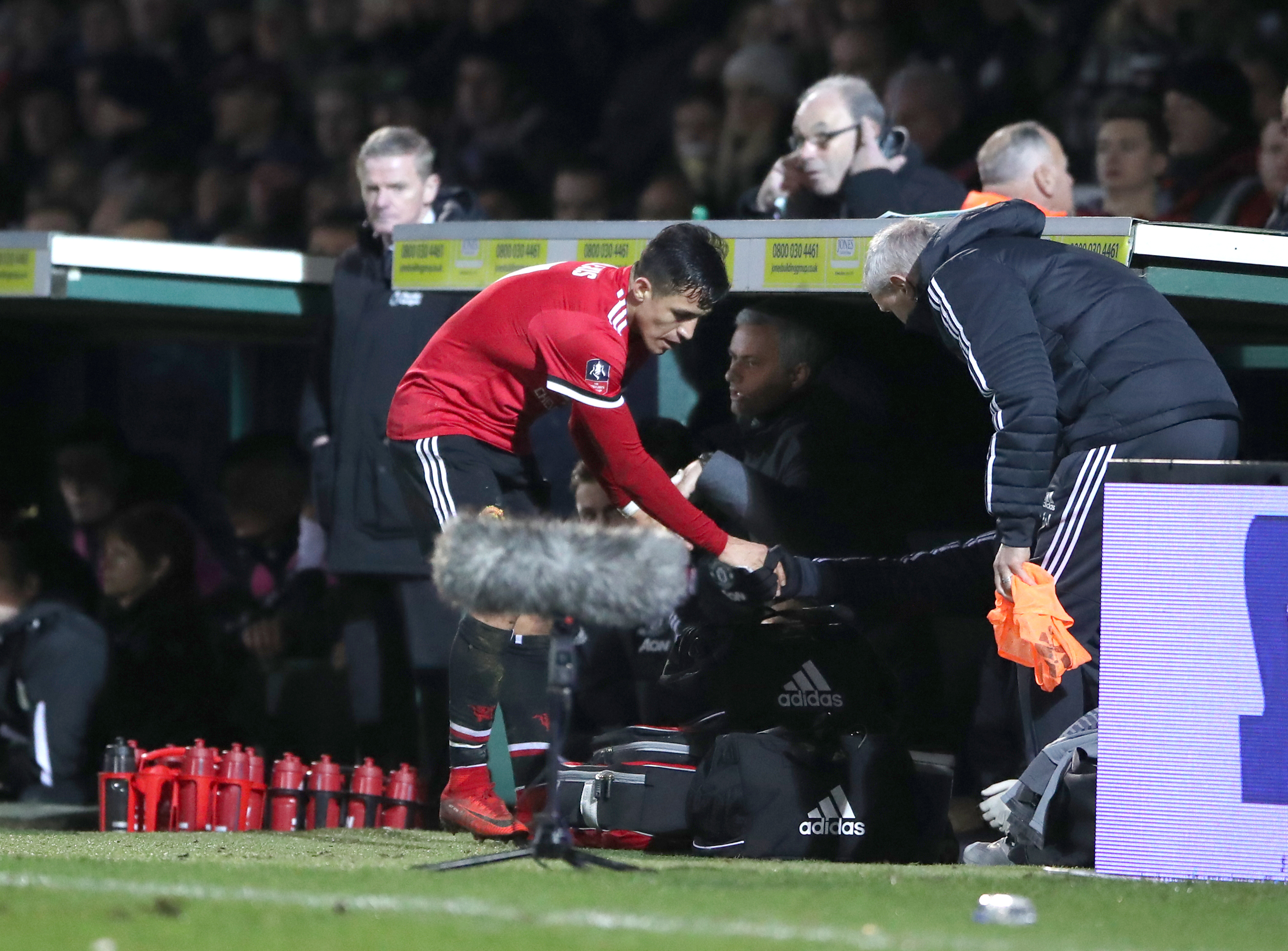 Alexis Sanchez joins Jose Mourinho in the Manchester United dugout after being substituted on his debut in the FA Cup tie against Yeovil Town (PA)
