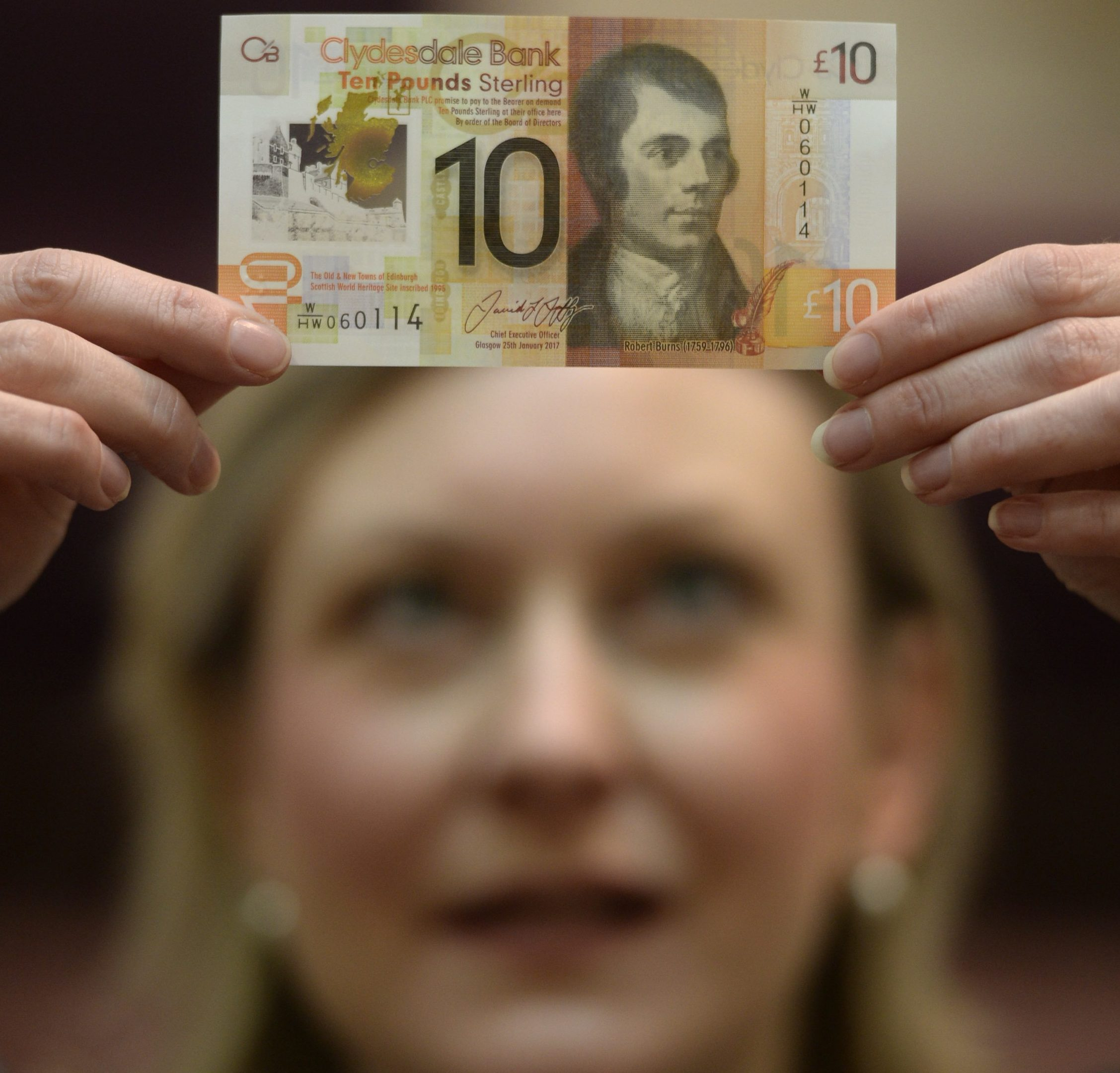 Clydesdale Bank company secretary Lorna McMillan admires the new £10 polymer bank note which is waterproof and twice as durable as paper bank notes at the company HQ in Glasgow, Scotland (SWNS)