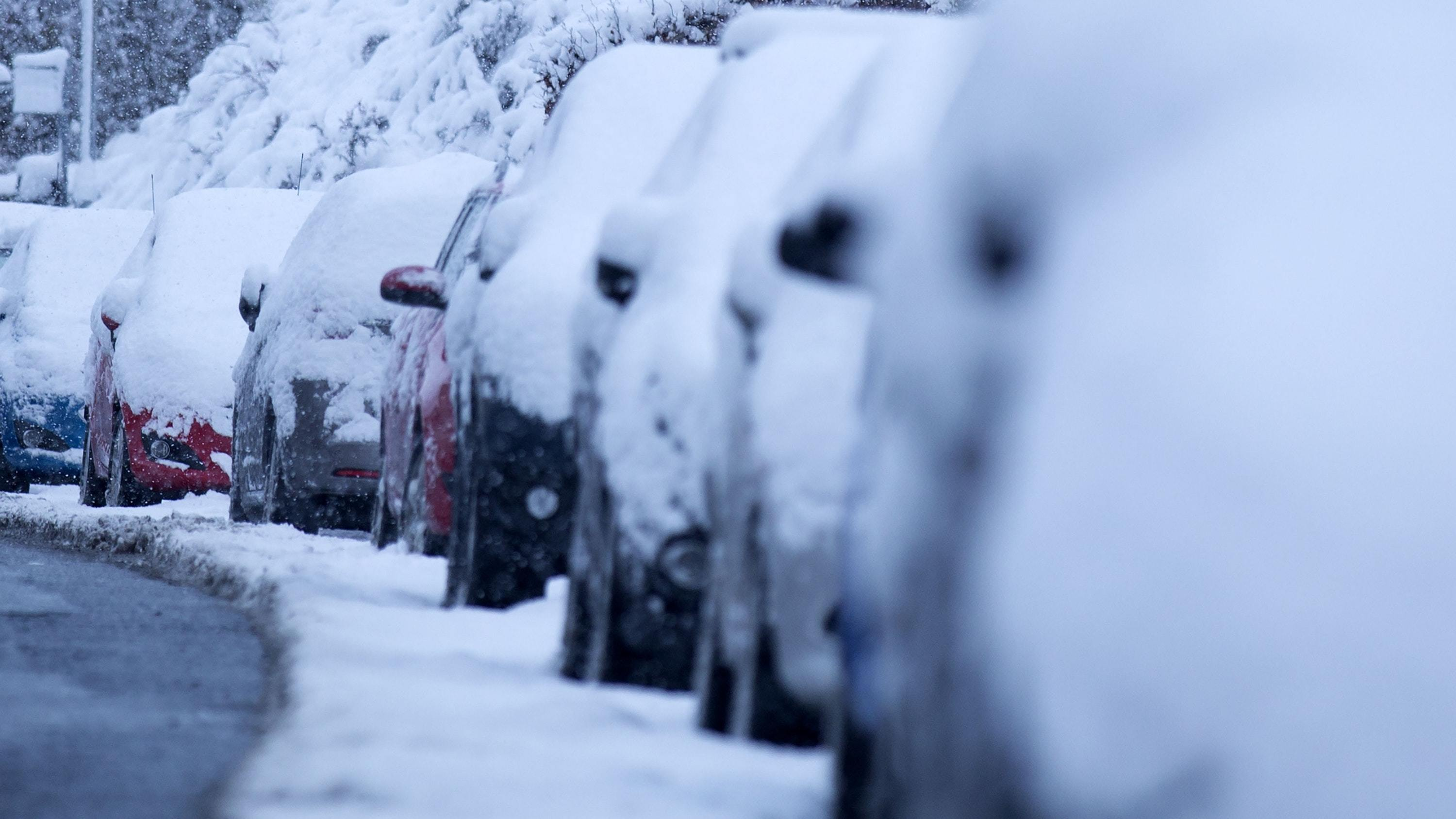 Cars covered with snow amid cold weather (David Cheskin/PA)