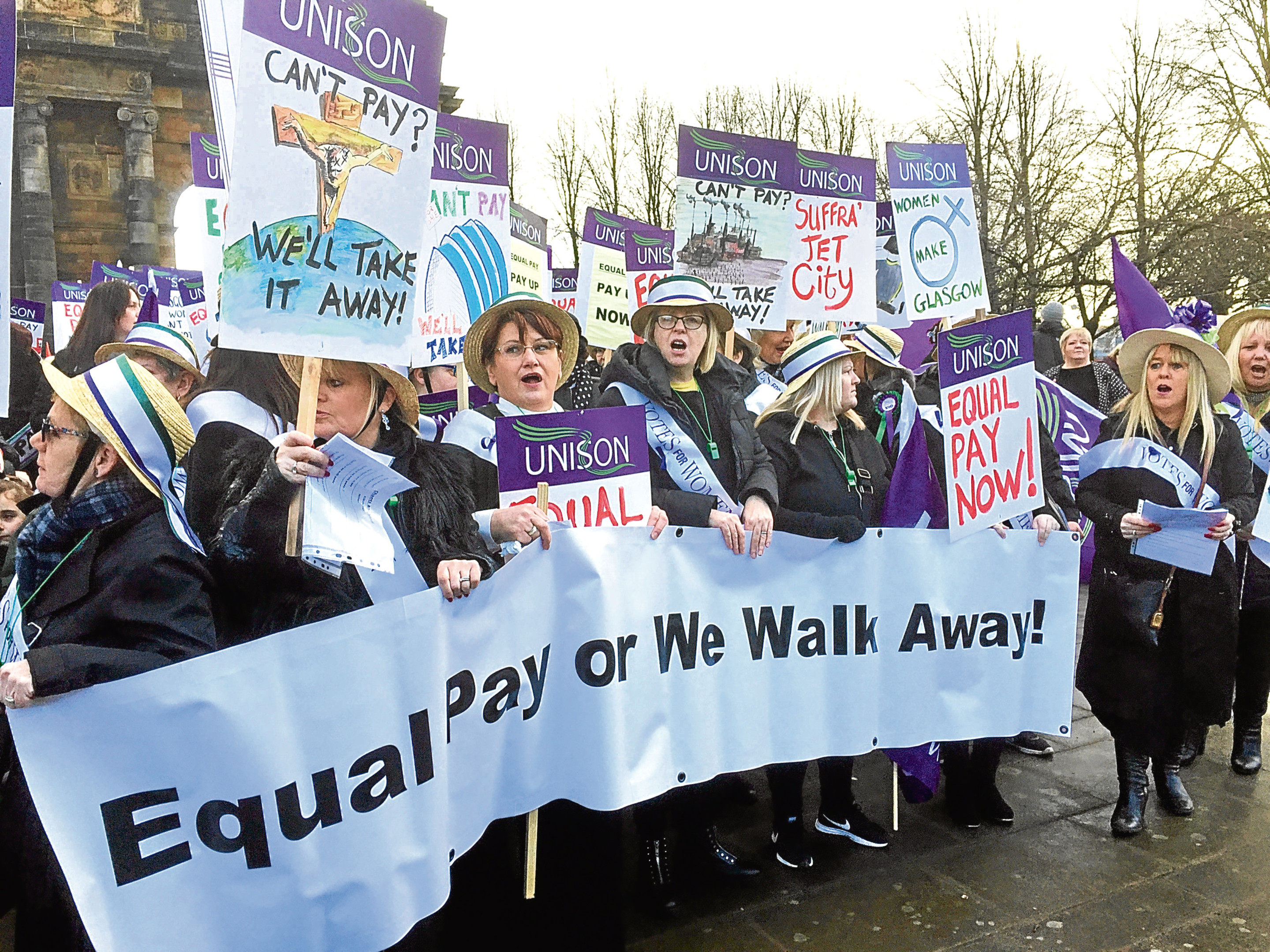 Hundreds of women, some dressed as suffragettes, march through Glasgow calling for equal pay from the city council (Lucinda Cameron / PA Wire)