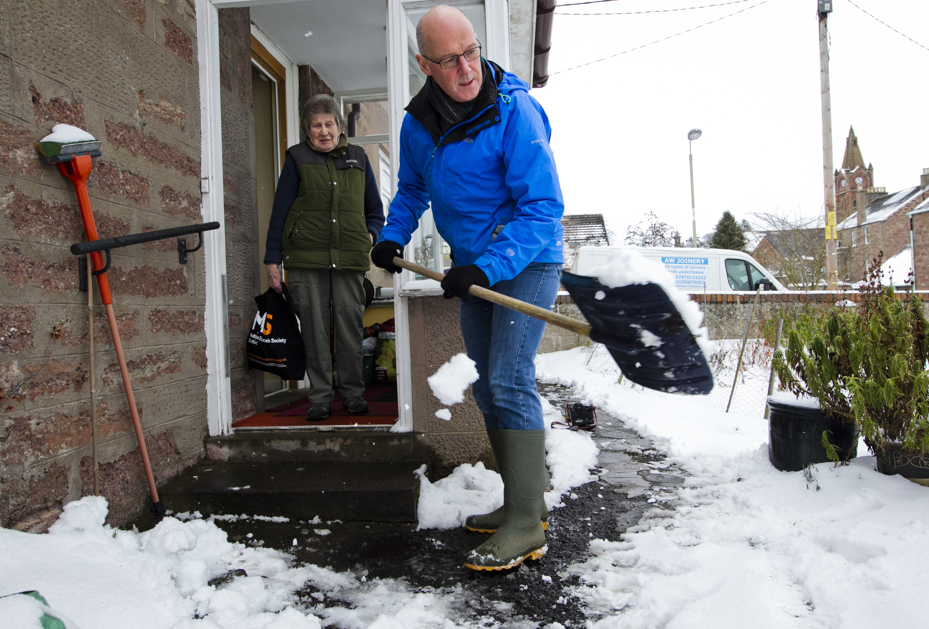 Deputy First Minister John Swinney clears the snow from Margaret Lindsay's path in Blairgowrie (Andrew Cawley / DC Thomson)