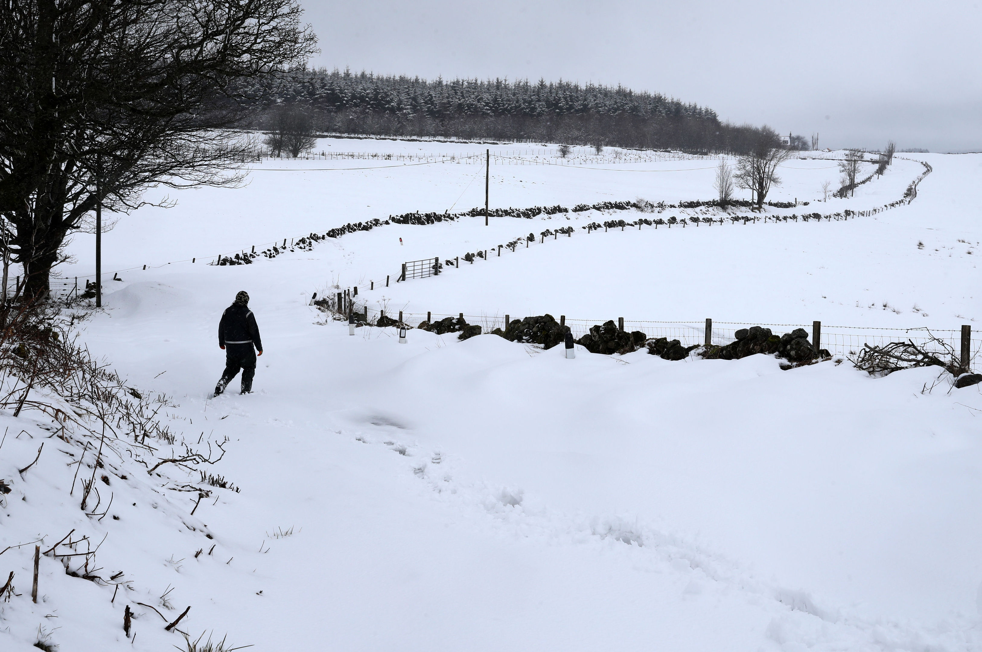 A person walks in deep snow in rural Carron Valley near Stirling, Scotland. (Andrew Milligan/PA Wire)