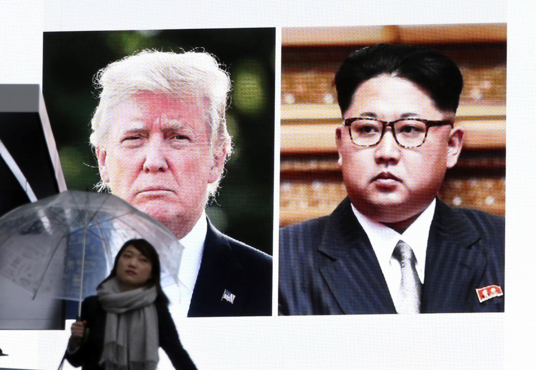 A woman walks by a huge screen showing Donald Trump and Kim Jong Un (Koji Sasahara/AP)