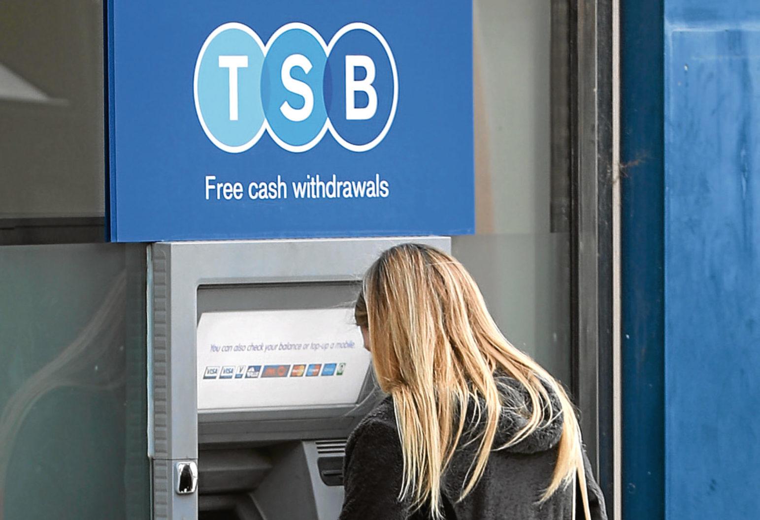 A woman uses a TSB cash machine (Gareth Fuller/PA Wire)
