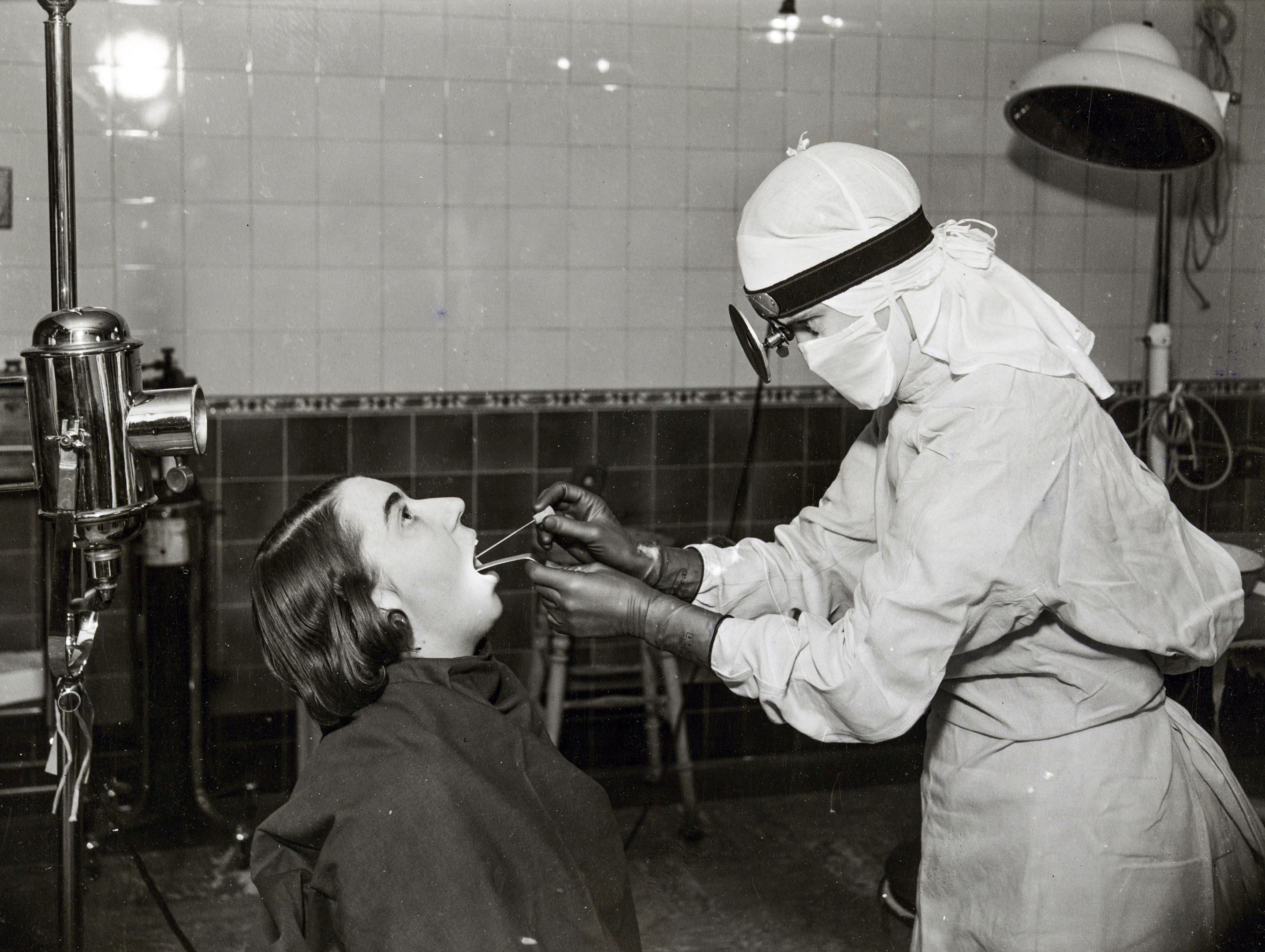 11/18/1941: A nurse in a white gown and cap taking a throat swab from a patient, at Middlesex Hospital (Historic England Archive /PA Wire)