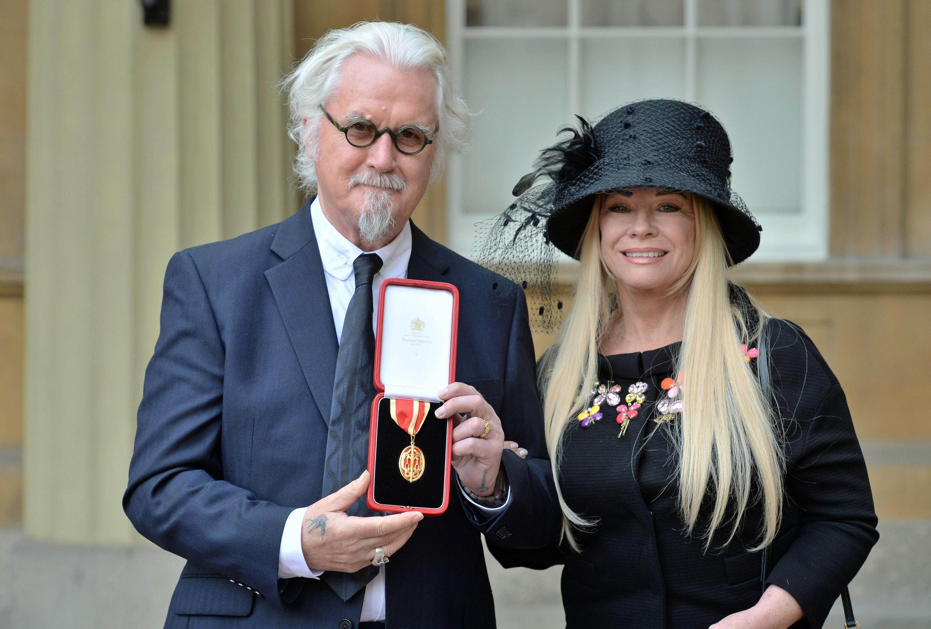 Sir Billy Connolly with his wife Pamela Stephenson after being knighted by the Duke of Cambridge during an Investiture ceremony at Buckingham Palace, London (PA)