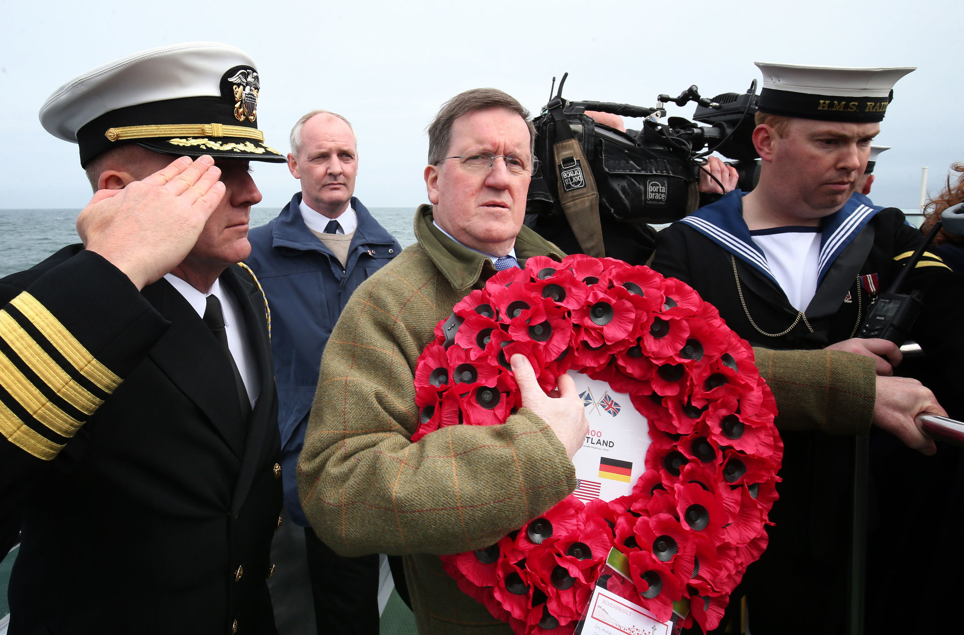 Lord George Robertson holds a wreath prior to throwing it in the sea close to the wreck of SS Tuscania (Jane Barlow/PA Wire)