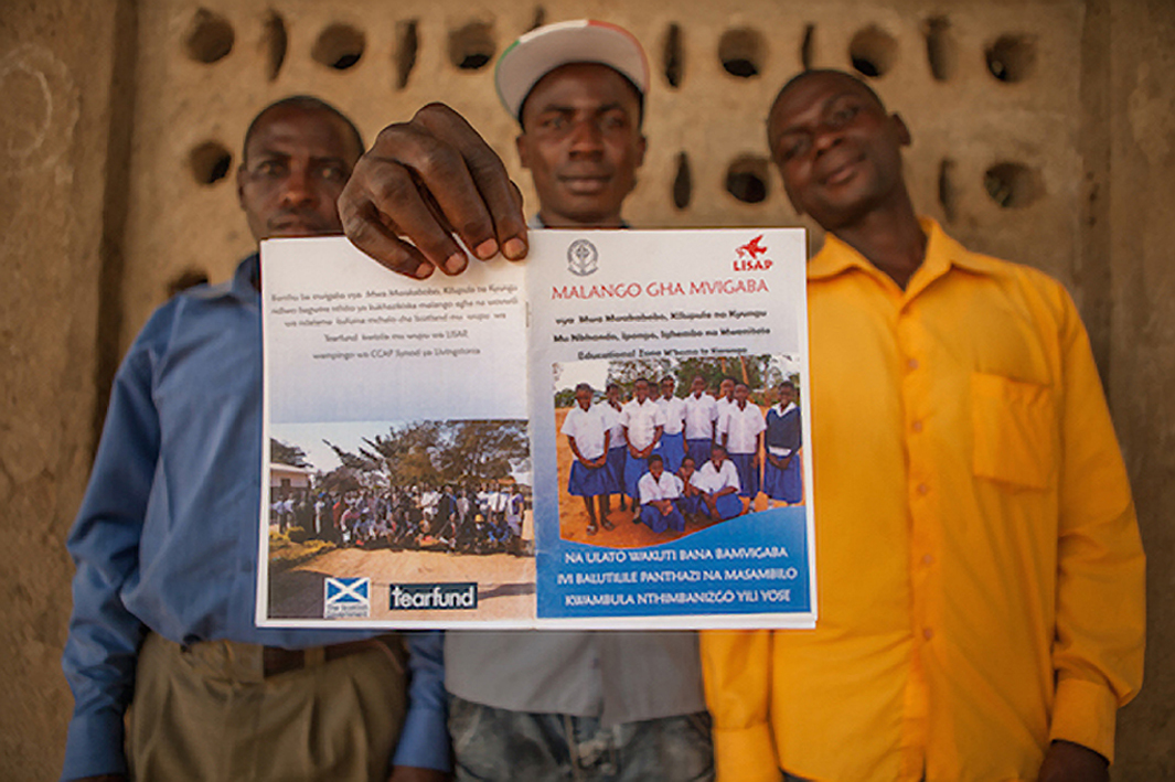 Village chiefs in Malawi hold up a leaflet carrying                         Tearfund and Scottish Government logos as part of work to eradicate child marriages (Chris Hoskins / TearFund)