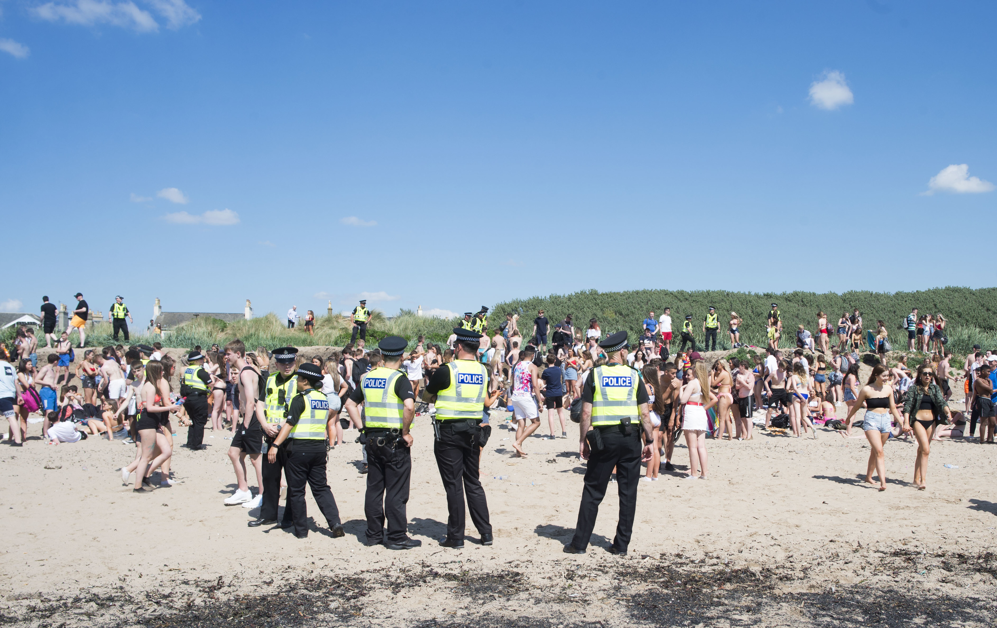 Police officers stand guard on Troon Beach last week as temperatures soar on Bank Holiday Monday (John Kirkby)