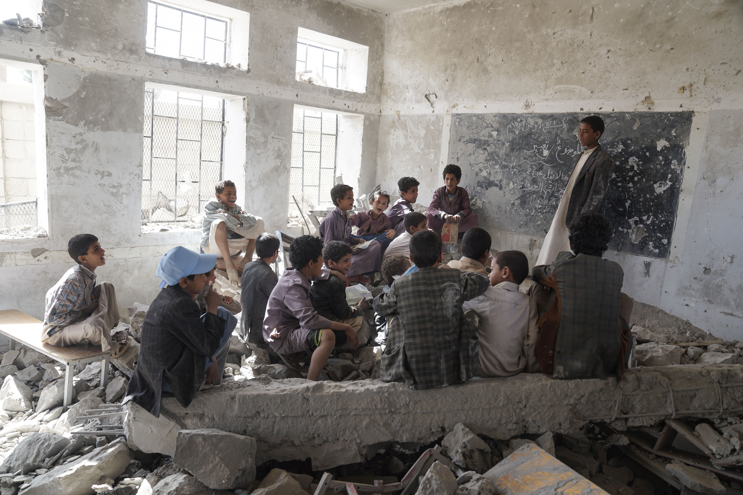 Children sit in a former classroom in the Aal Okab school in Yemen which was bombed out in 2015 (Giles Clarke for UN OCHA / Getty Images)