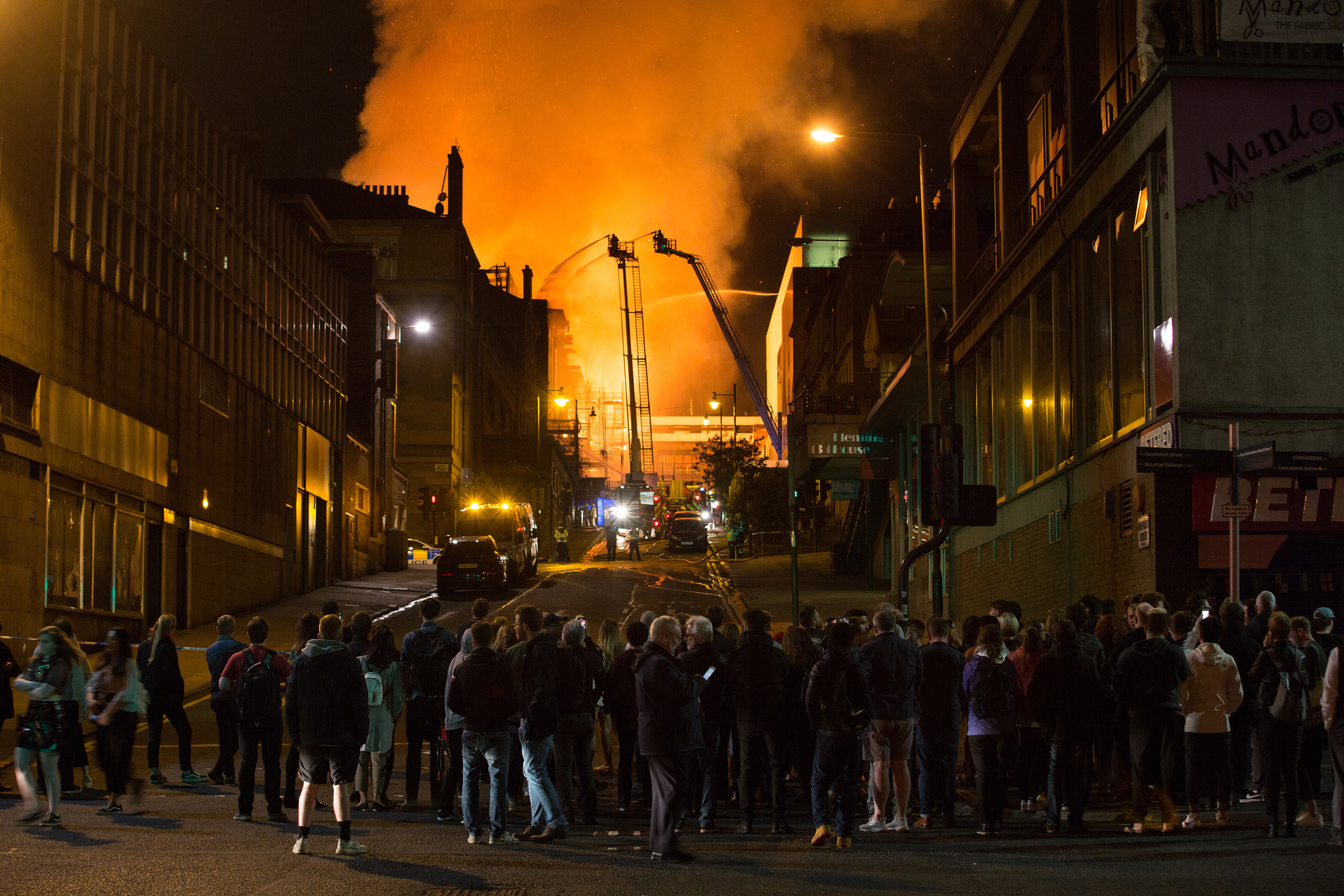 Onlookers huddle to watch the fire crews at work as fire engulfs the art school while the sky over Glasgow city centre glows from the flames last month (Robert Perry/Getty Images)