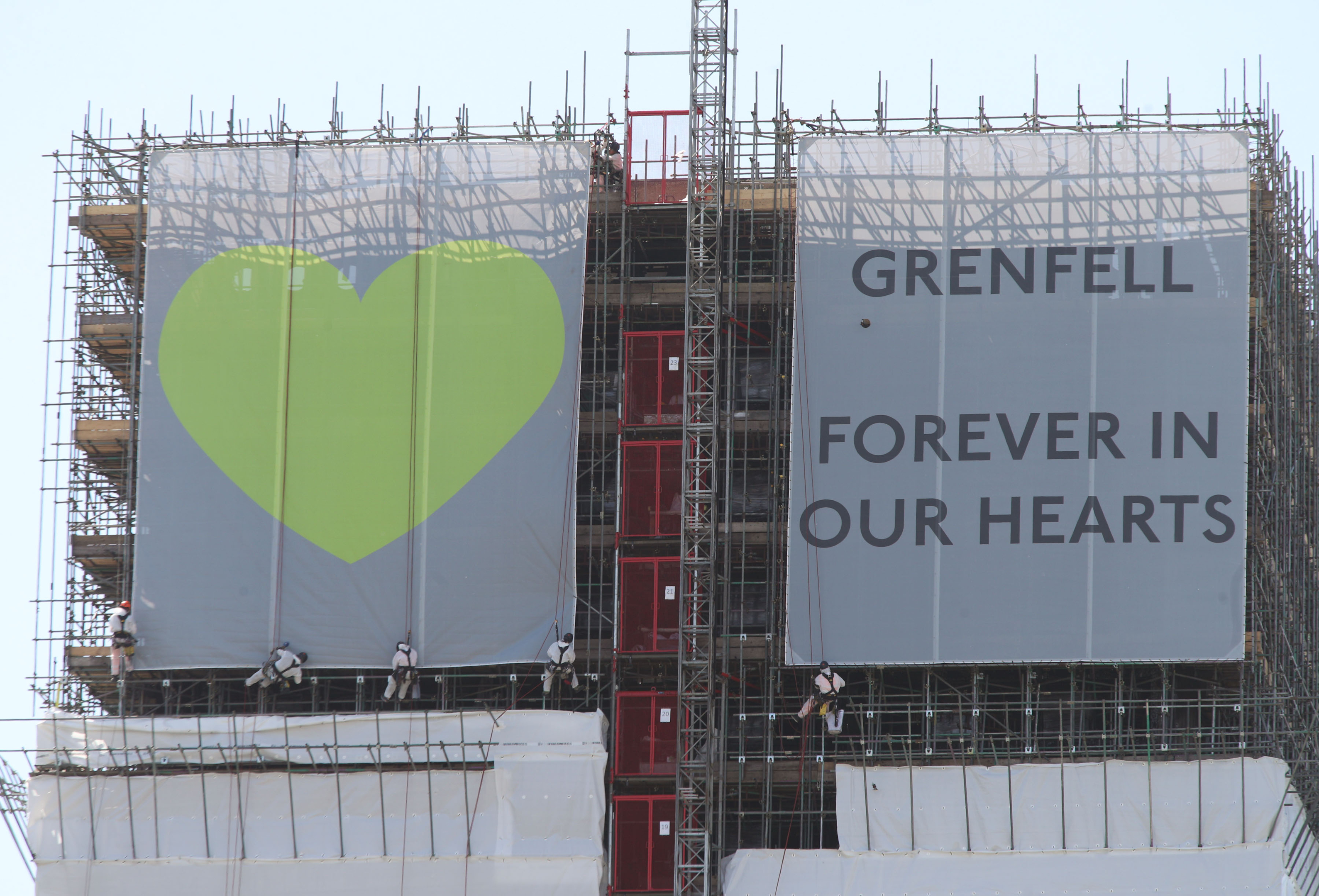 Banners are unveiled on the outside of Grenfell Tower in west London (Yui Mok / PA Wire)