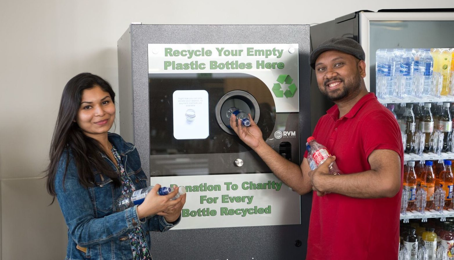 (L-R) Students Tahsina Akbar, 28, and Ahmed Prapan, 27, are the first to try out the University's new Reverse Vending machine.