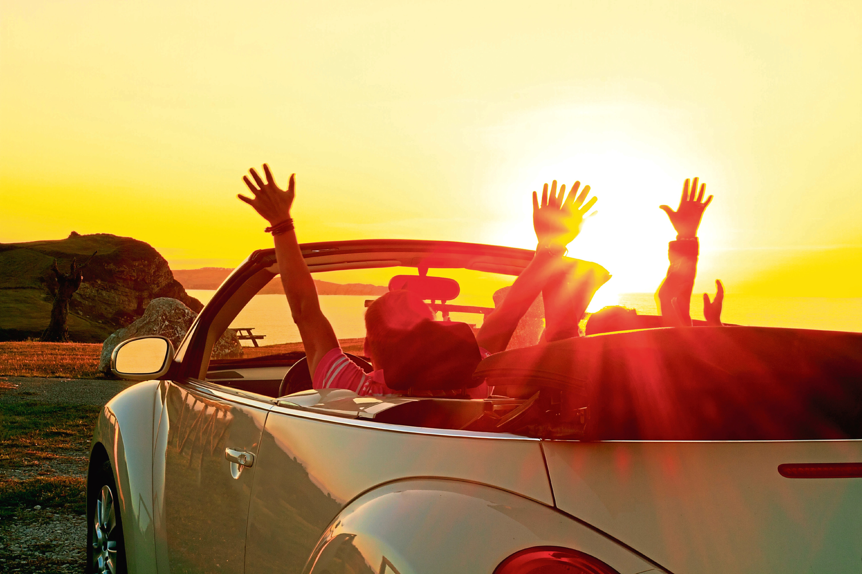 DEH00A Happy family in a cabriolet convertible car at the sunset in summer