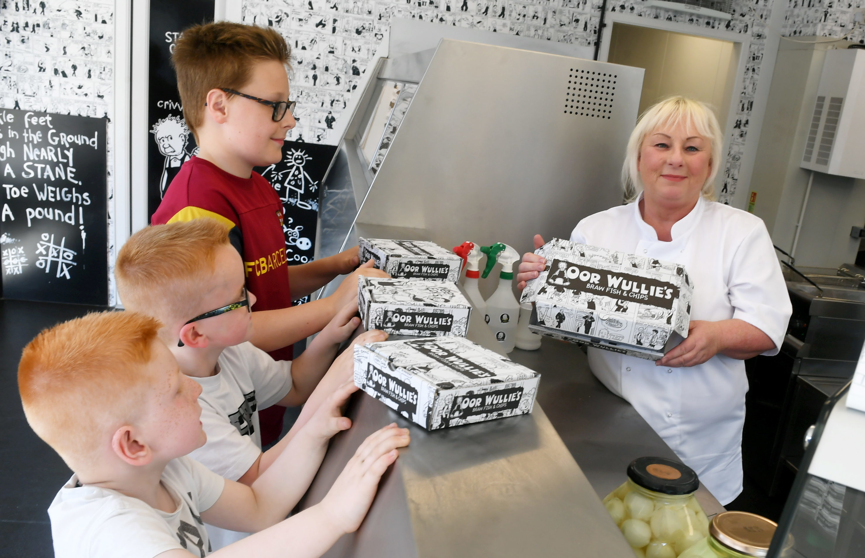 Sylvia Milne serving the first customers, from left, brothers, Lawrence, 11, Zak, 6 and Levi Jaffrey, 6 (Chris Sumner / DC Thomson)