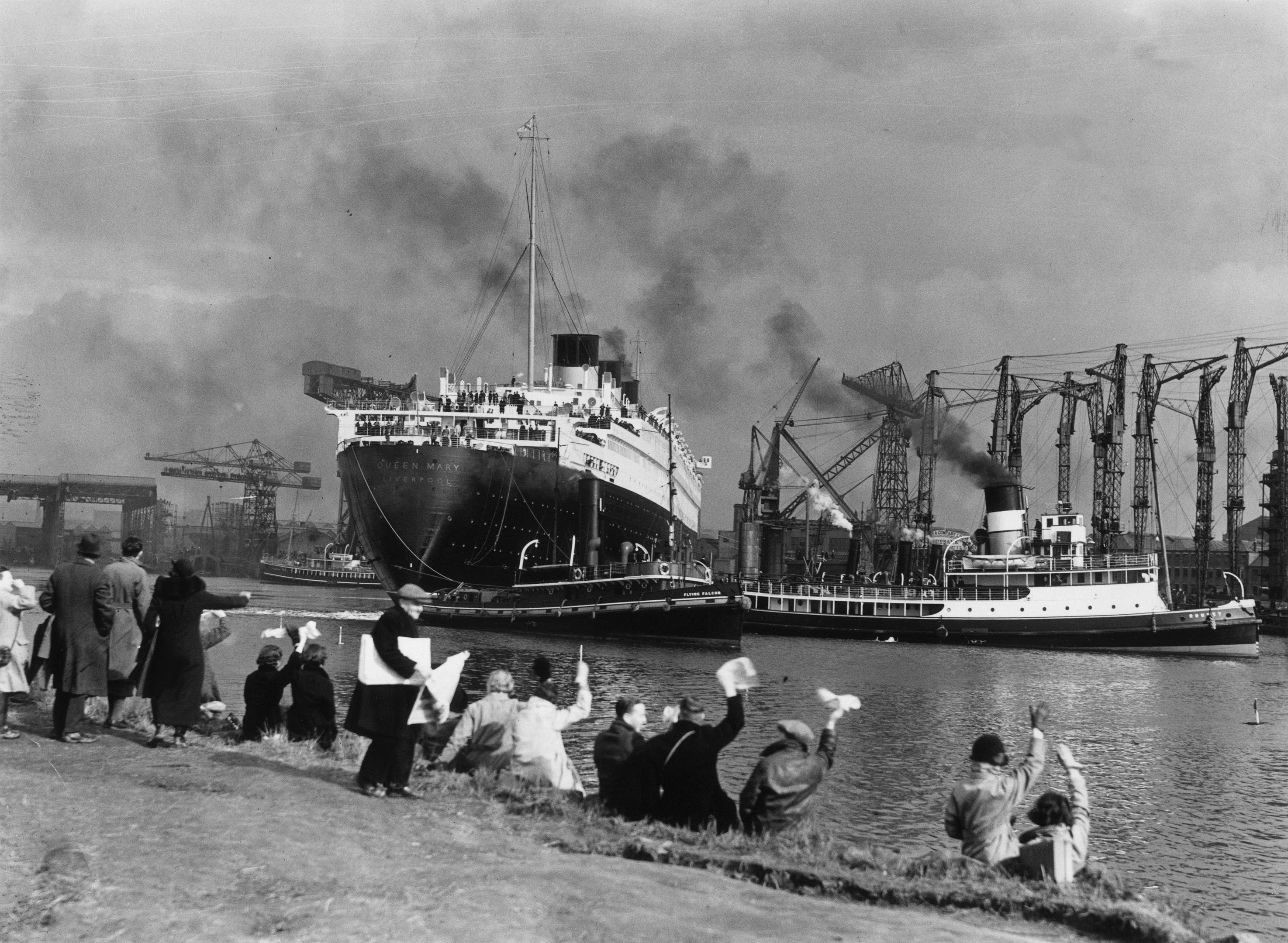 Crowds gather to watch the new Cunard White Star liner Queen Mary leaving her fitting-out berth a couple of years after the launch (Topical Press Agency/Getty Images)