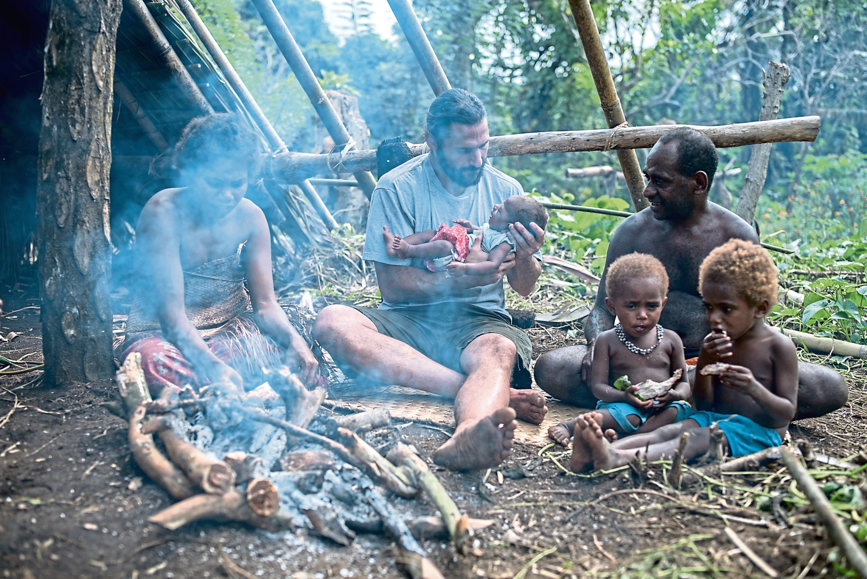 Vanuatu - Hazen holding a newborn child alongside the Salkon Chief Atkins family. (National Geographic/Jimmy Cape)