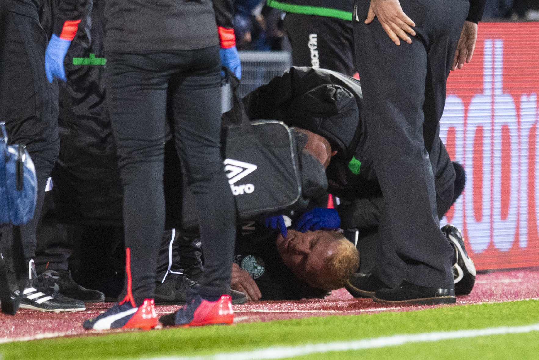 Hibernian manager Neil Lennon lies on the ground after being struct by an object from the crowd (SNS Group / Craig Williamson)