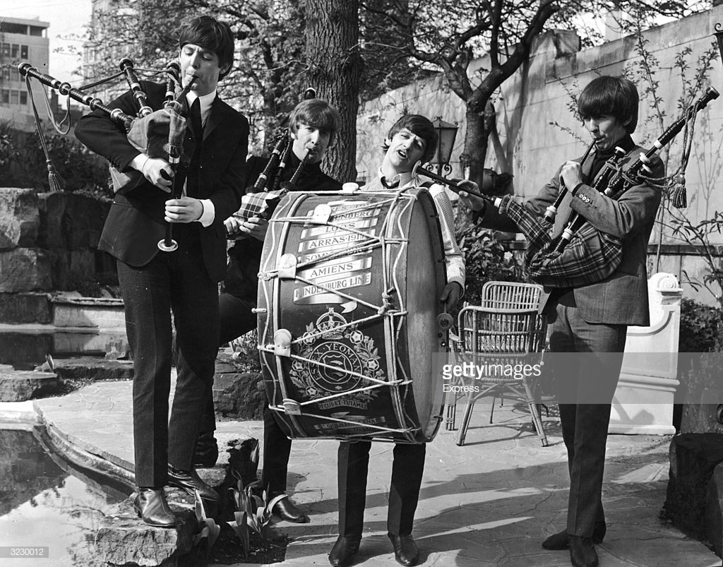 British rock group The Beatles perform on bagpipes and marching drum outdoors to promote their concerts in the Scottish cities of Glasgow and Edinburgh. L-R: Paul McCartney, John Lennon (1940 - 1980), Ringo Starr (beating the drum) and George Harrison (1943 - 2001).  (Express/Getty Images)