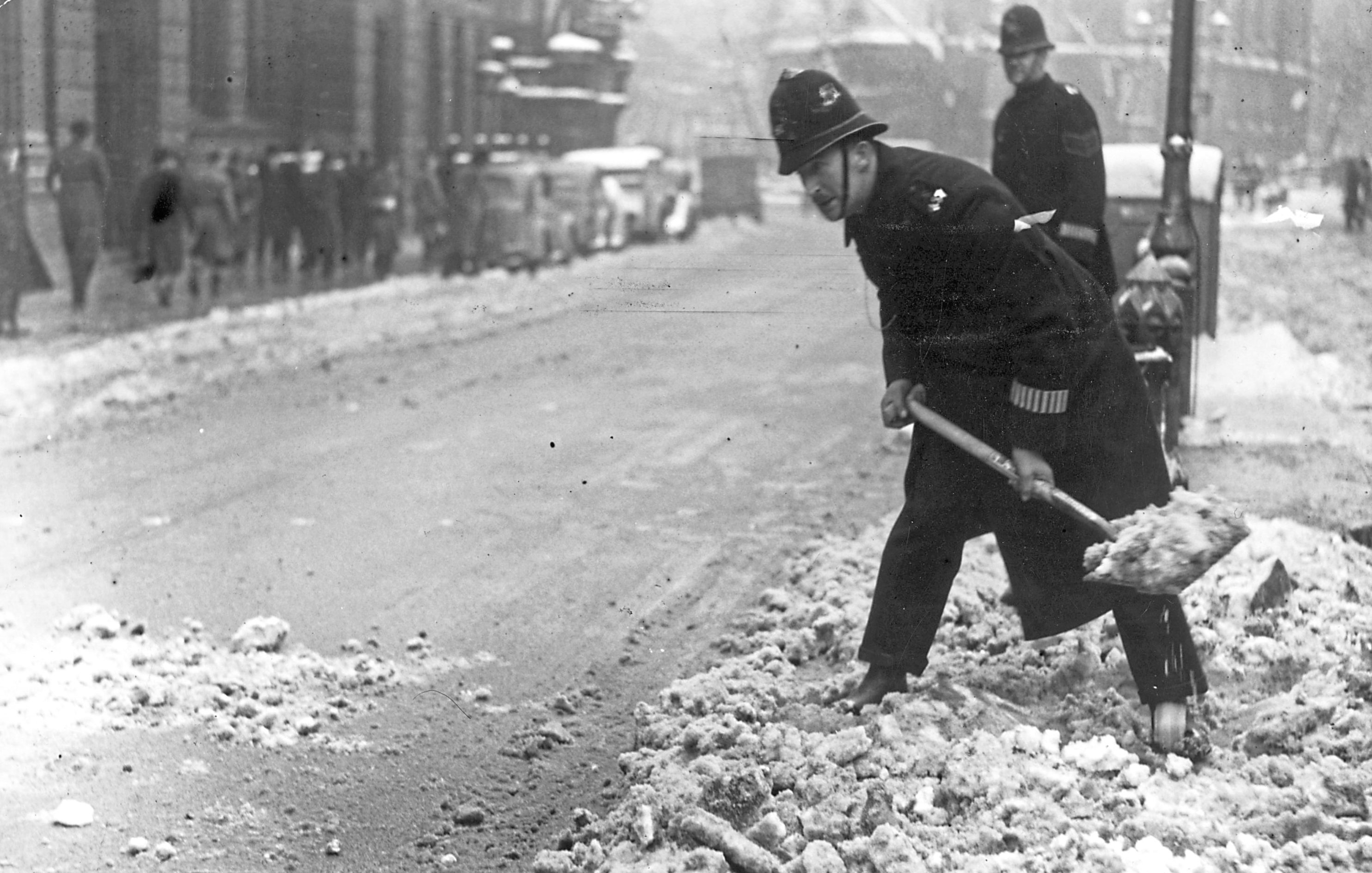 10th March 1947:  A London policeman clears away some heavy snowfall  (Monty Fresco/Topical Press Agency/Getty Images)