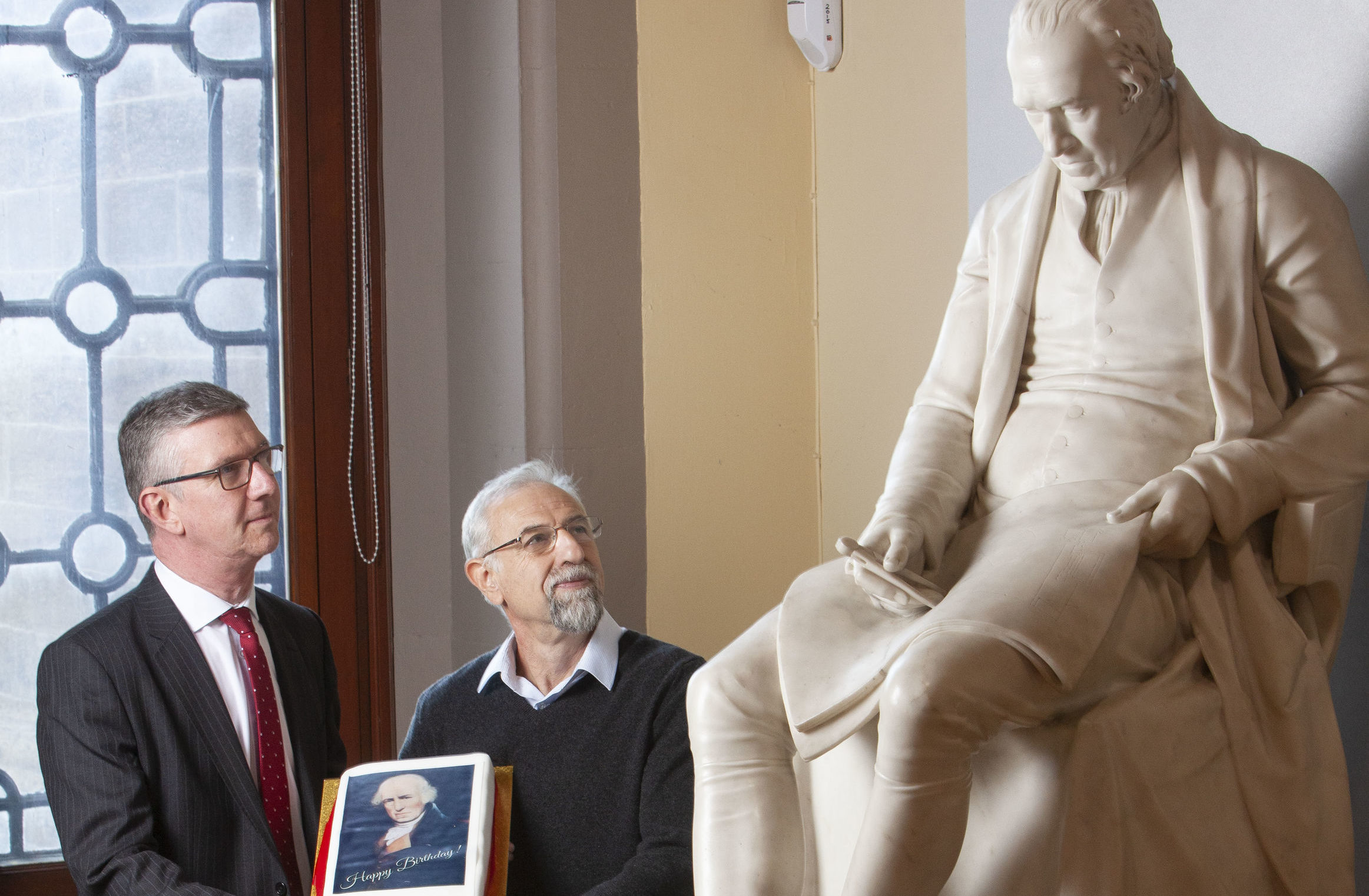 Professor Colin McInnes (left) and Professor Asen Asenov next to a statue of James Watt (University of Glasgow/PA Wire)