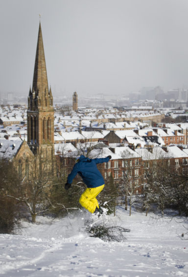 A man snowboarding in Glasgow's Queens Park