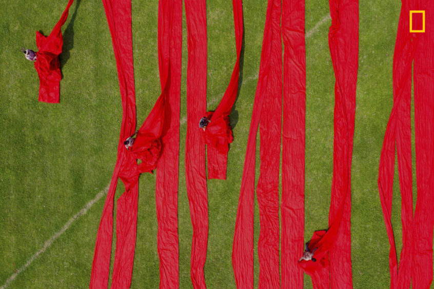 PHOTO AND CAPTION BYMD TANVEER ROHAN/ 2019 NATIONAL GEOGRAPHIC TRAVEL PHOTO CONTESTBangladeshi workers dry dyed, bright-red cloth across a field under the sun near Dhaka, Bangladesh. These people work for the cloth industry and each day they earn five to seven dollars for their work. First they color the cloths by traditional methods. After that, theyput the cloths on an open field to dry under the sun.