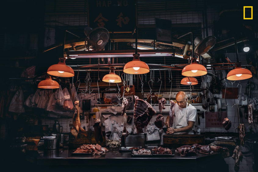 PHOTO AND CAPTION BYANTÓNIO LEONG/ 2019 NATIONAL GEOGRAPHIC TRAVEL PHOTO CONTESTA local butcher is seen preparing to close his shop.