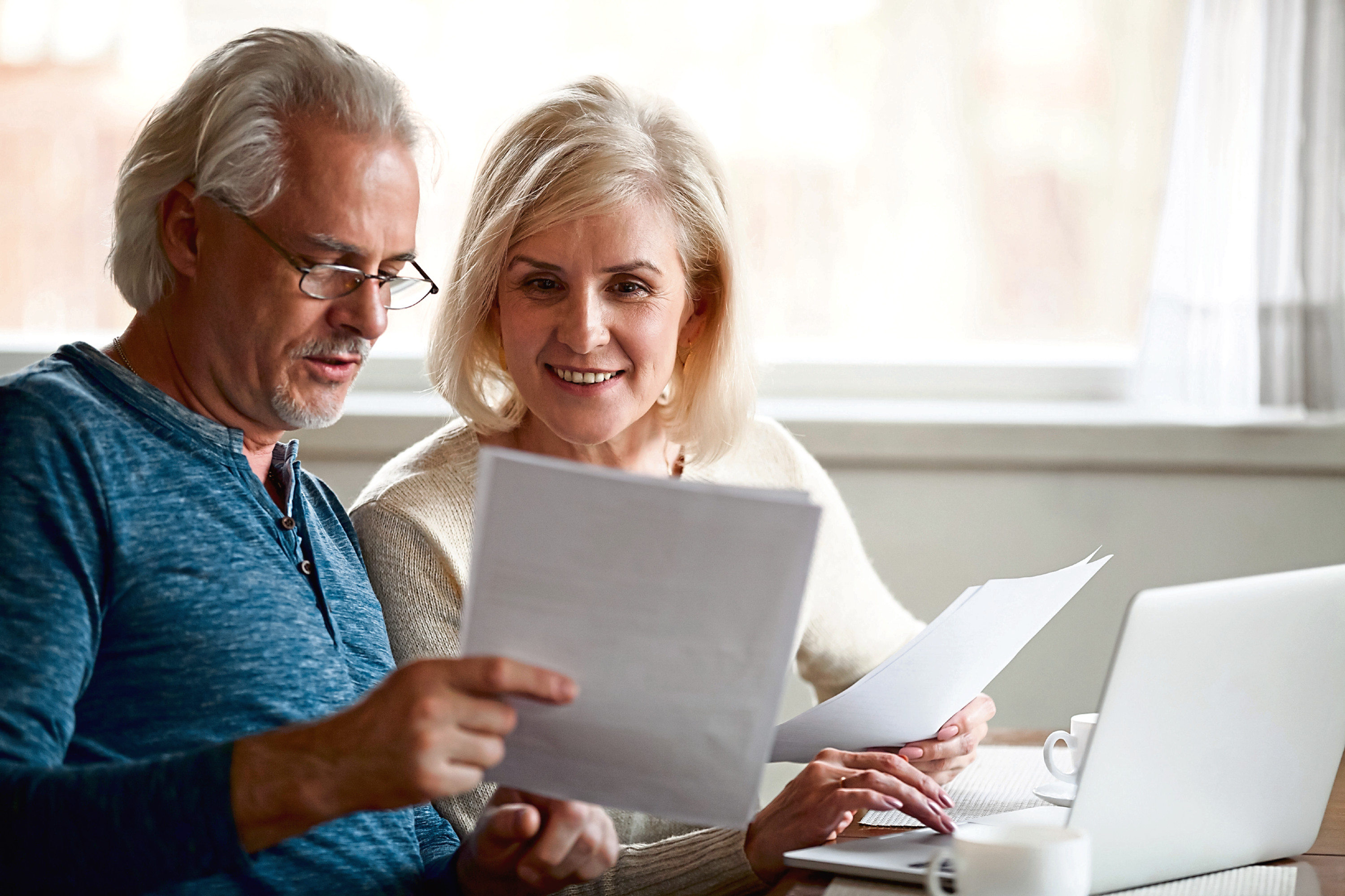 Happy old middle aged couple holding reading good news in document, smiling senior mature family excited by mail letter, checking paying domestic bills online on laptop, discussing budget planning