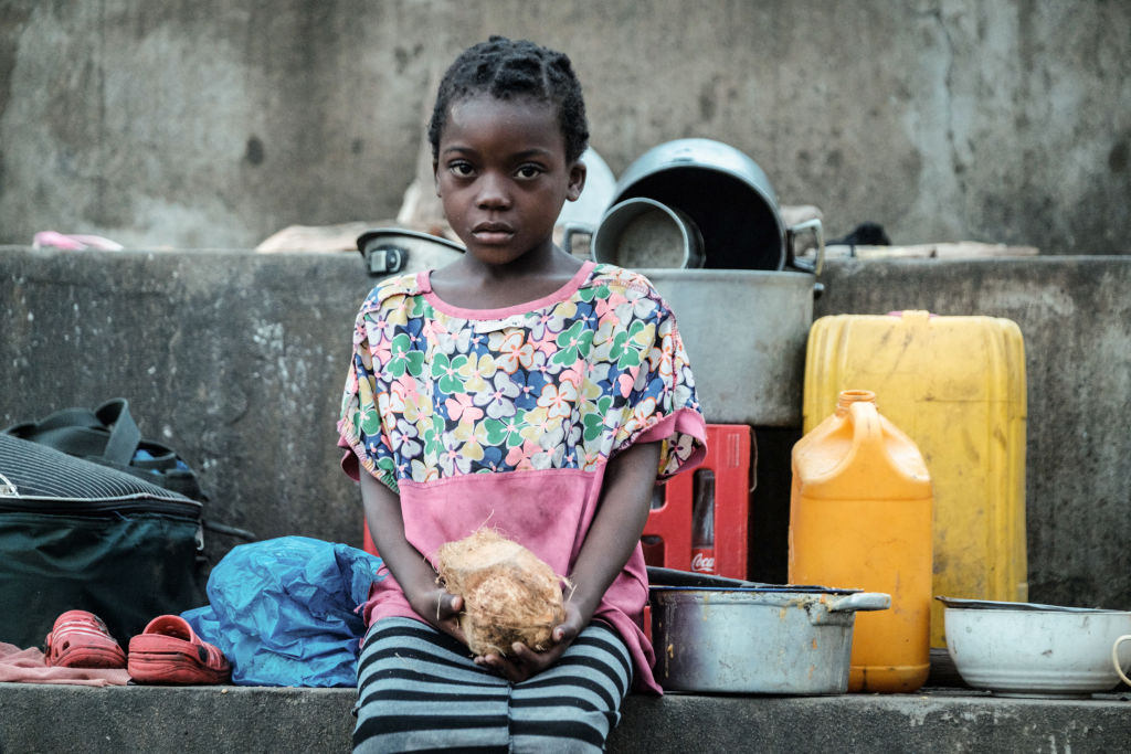 TOPSHOT - Elena Joaquin, 6, holds a coconut as she stays in shelter with her family at the stands of Ring ground in Buzi, Mozambique, on March 23, 2019. - The death toll in Mozambique on March 23, 2019 climbed to 417 after a cyclone pummelled swathes of the southern African country, flooding thousands of square kilometres, as the UN stepped up calls for more help for survivors. Cyclone Idai smashed into the coast of central Mozambique last week, unleashing hurricane-force winds and rains that flooded the hinterland and drenched eastern Zimbabwe leaving a trail of destruction. (Yasuyoshi CHIBA / AFP)
