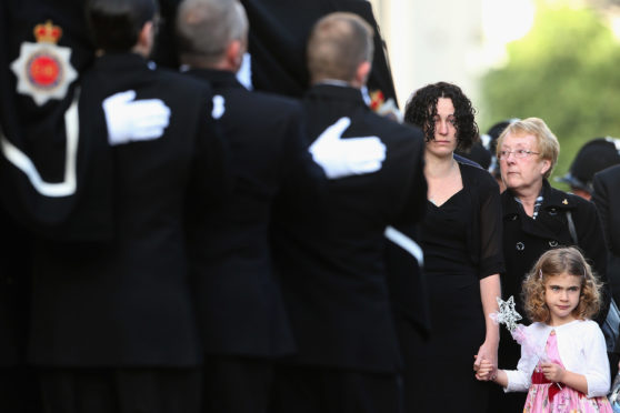 Clare Curran, the partner of murdered police officer Fiona Bone and five-year-old daughter Jessie watch as the coffin of the Greater Manchester Police constable is taken into Manchester Cathedral for her funeral service